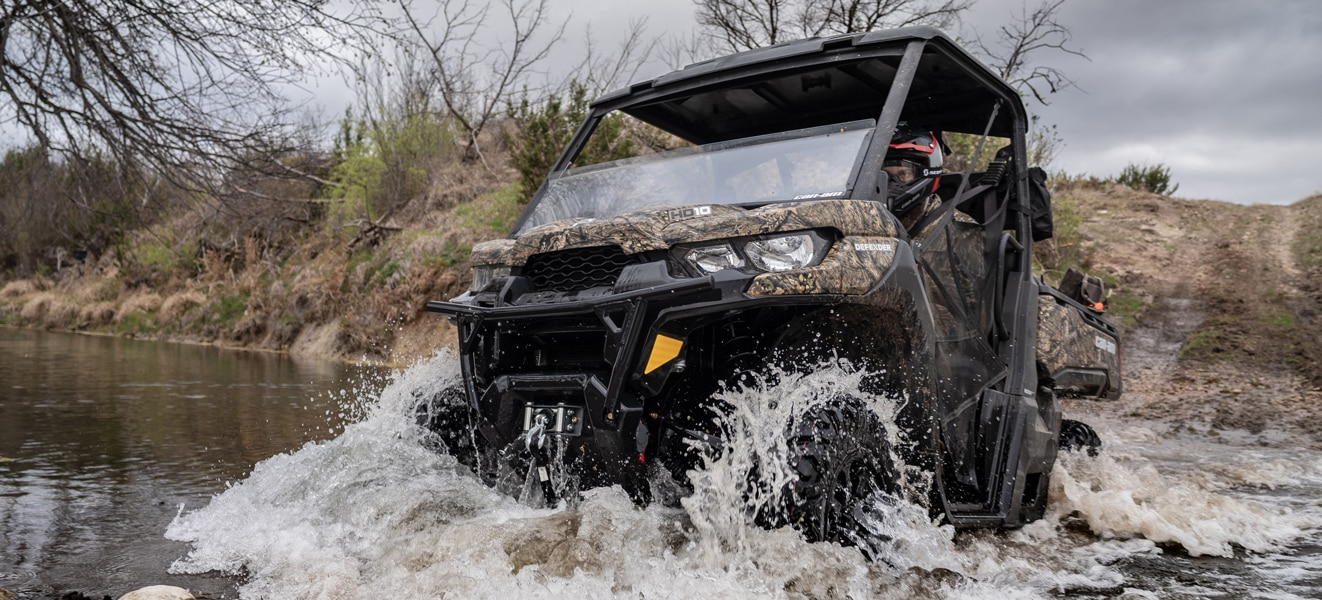Man crossing stream with a Can-Am Defender Mossy Oak Edition
