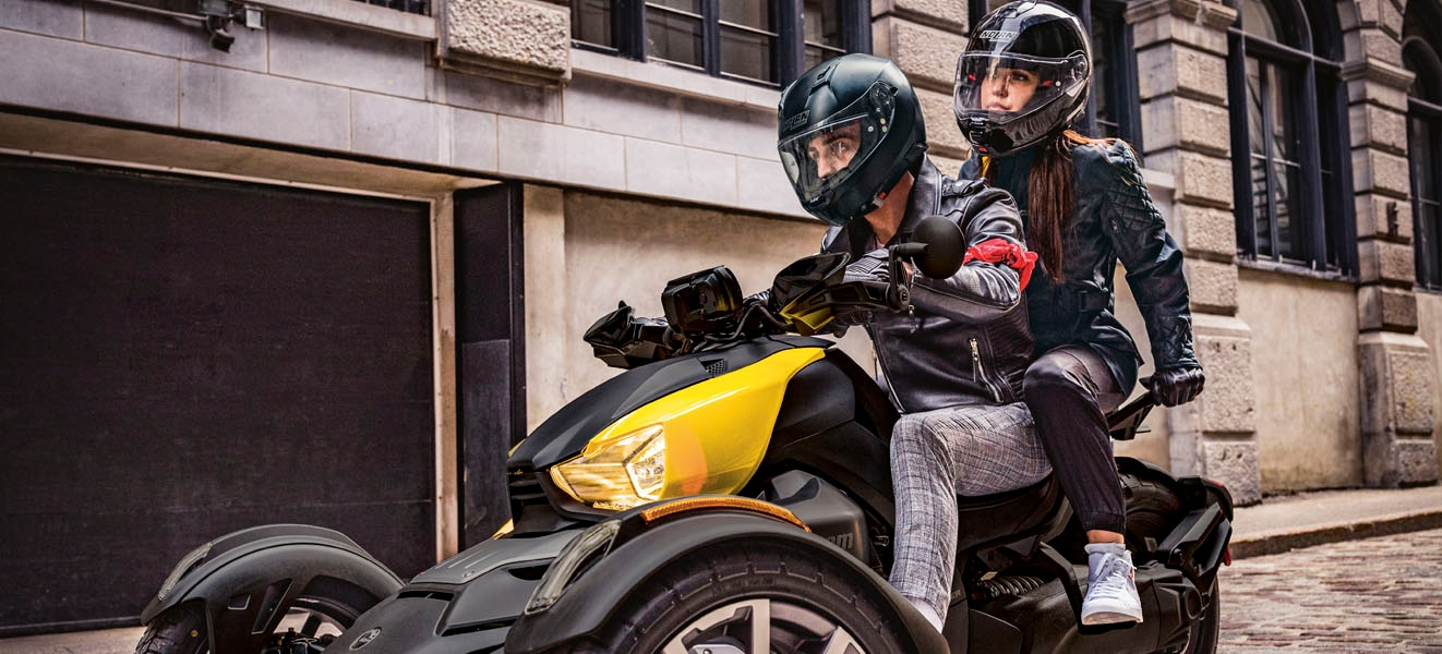 Couple riding on a Ryker with yellow panels through the city streets.