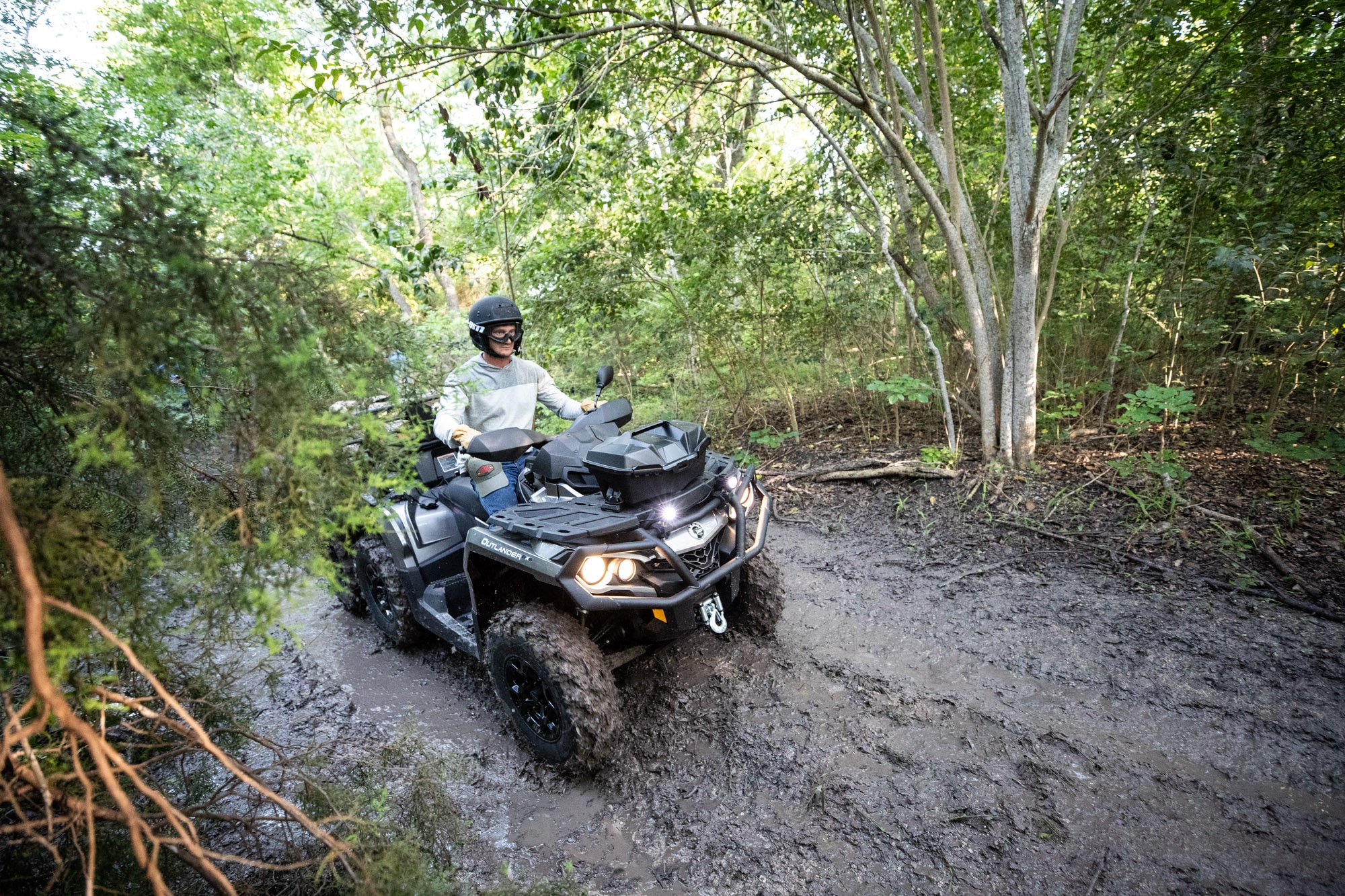 Man riding a Can-Am Outlander 6x6 XT ATV in the mud with wood in the rear rack