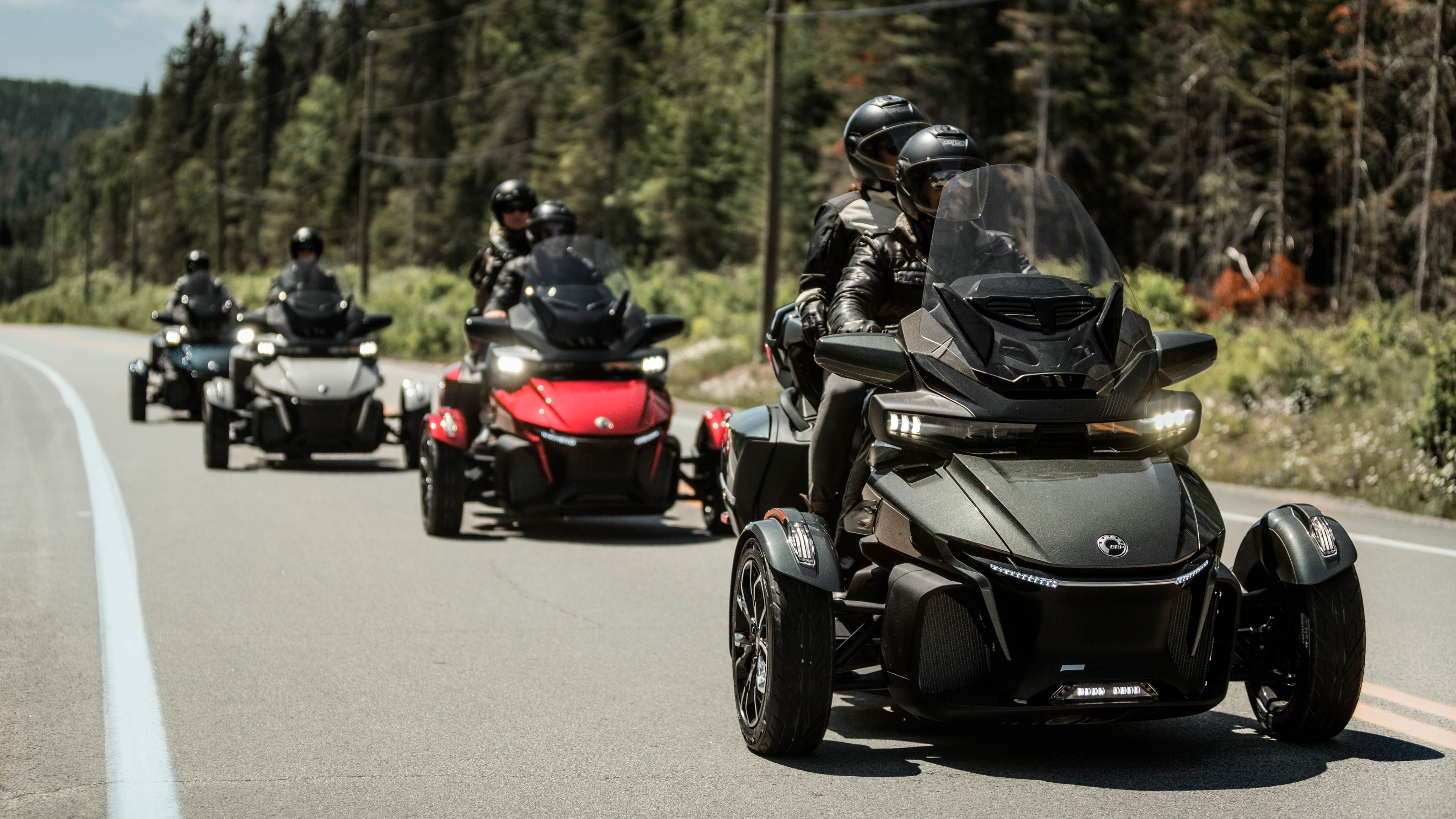 Four 2020 Can-Am Spyder RT vehicles riding on the open road