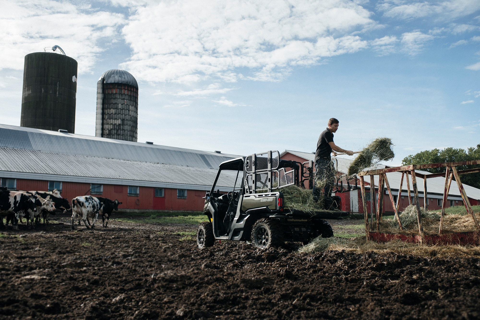 A man doing farm work with his Can-Am Defender XT side-by-side