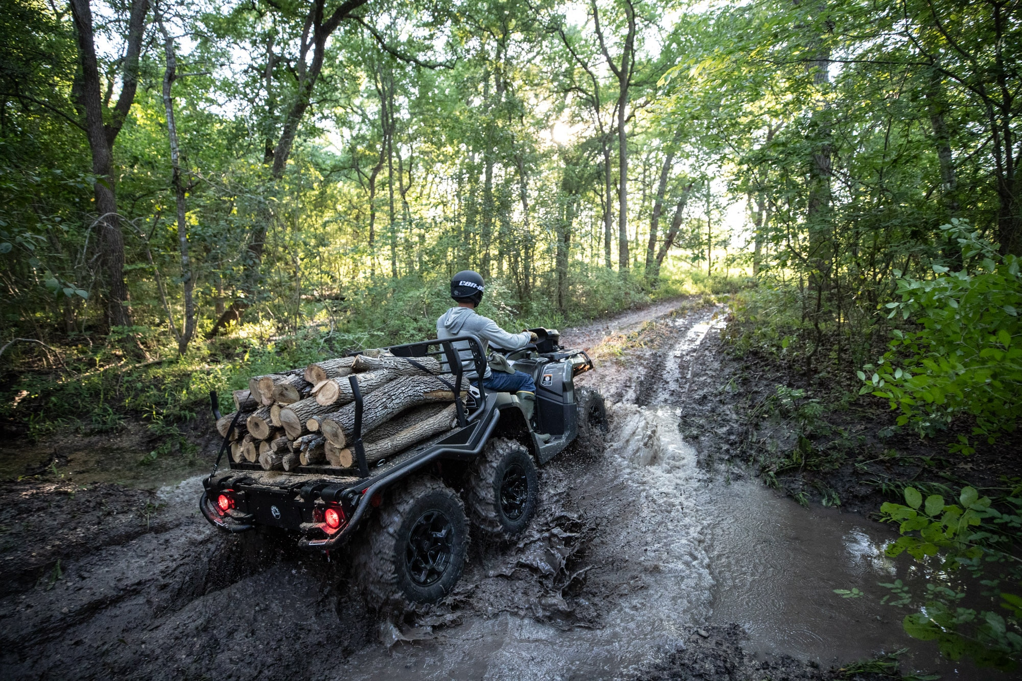 Man riding a Can-Am Outlander 6x6 ATV in the mud with wood in the rear rack
