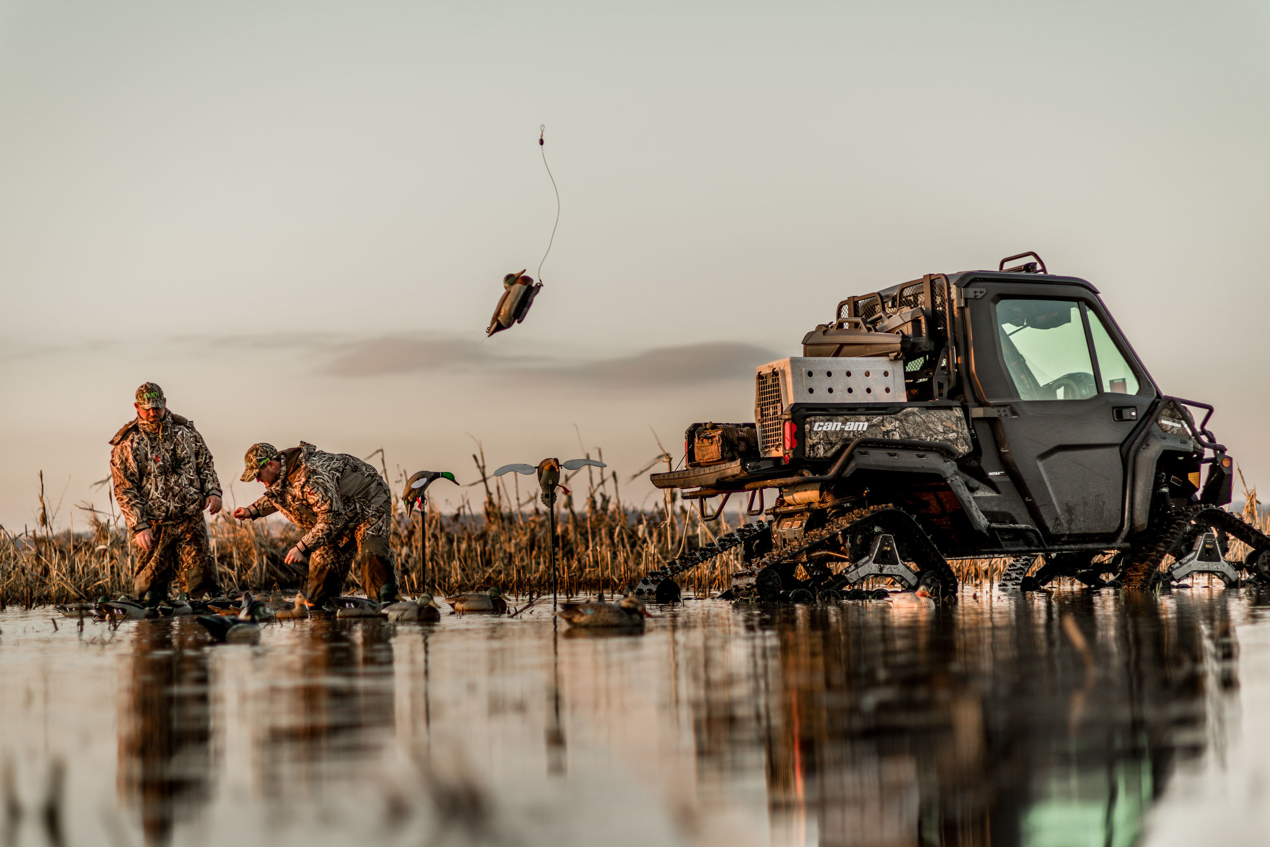 Two hunters with their feet in the water next to a custom hunting Can-Am Defender side-by-side