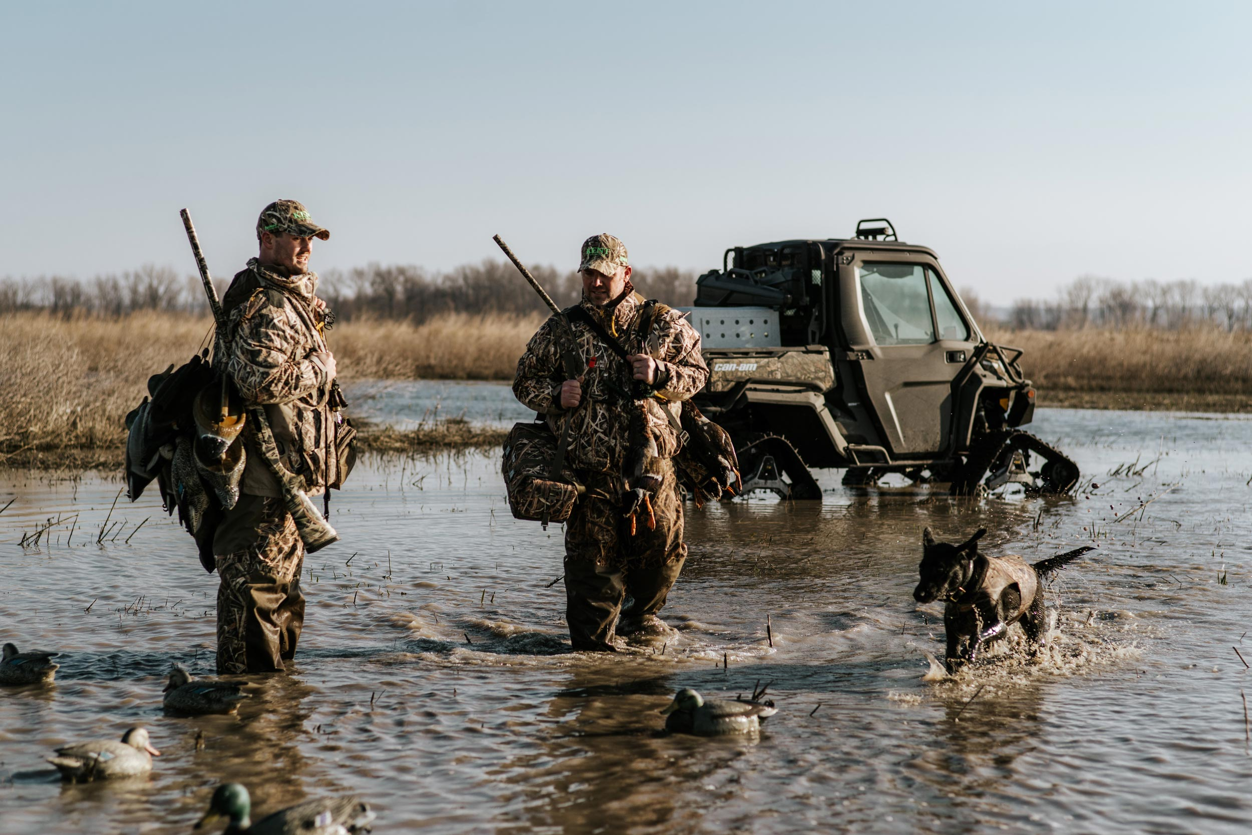 Two hunters with a dog in the water with a custom Can-Am Defender Mossy Oak Edition in the background
