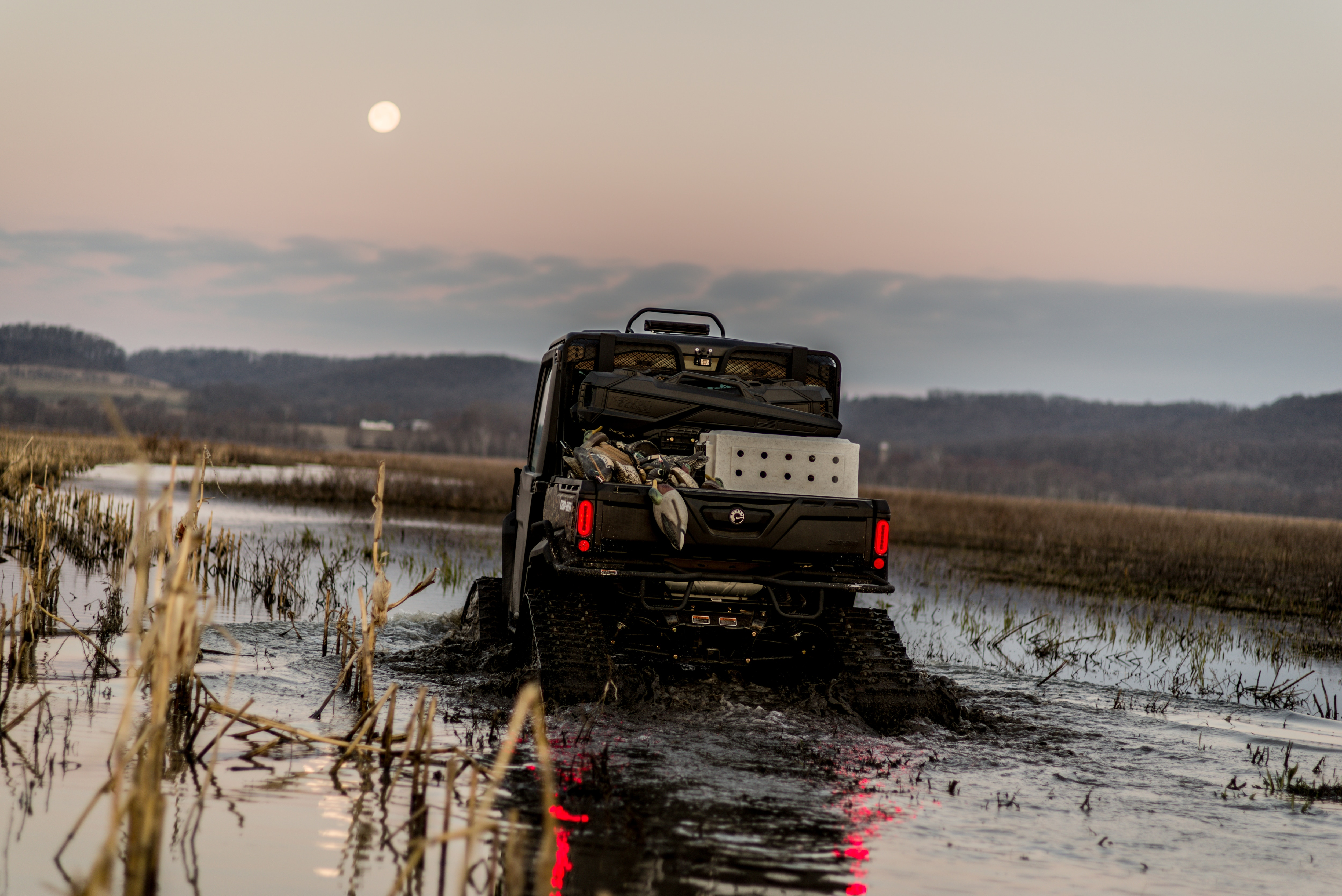 Rear view of a custom hunting Can-Am Defender rolling in water