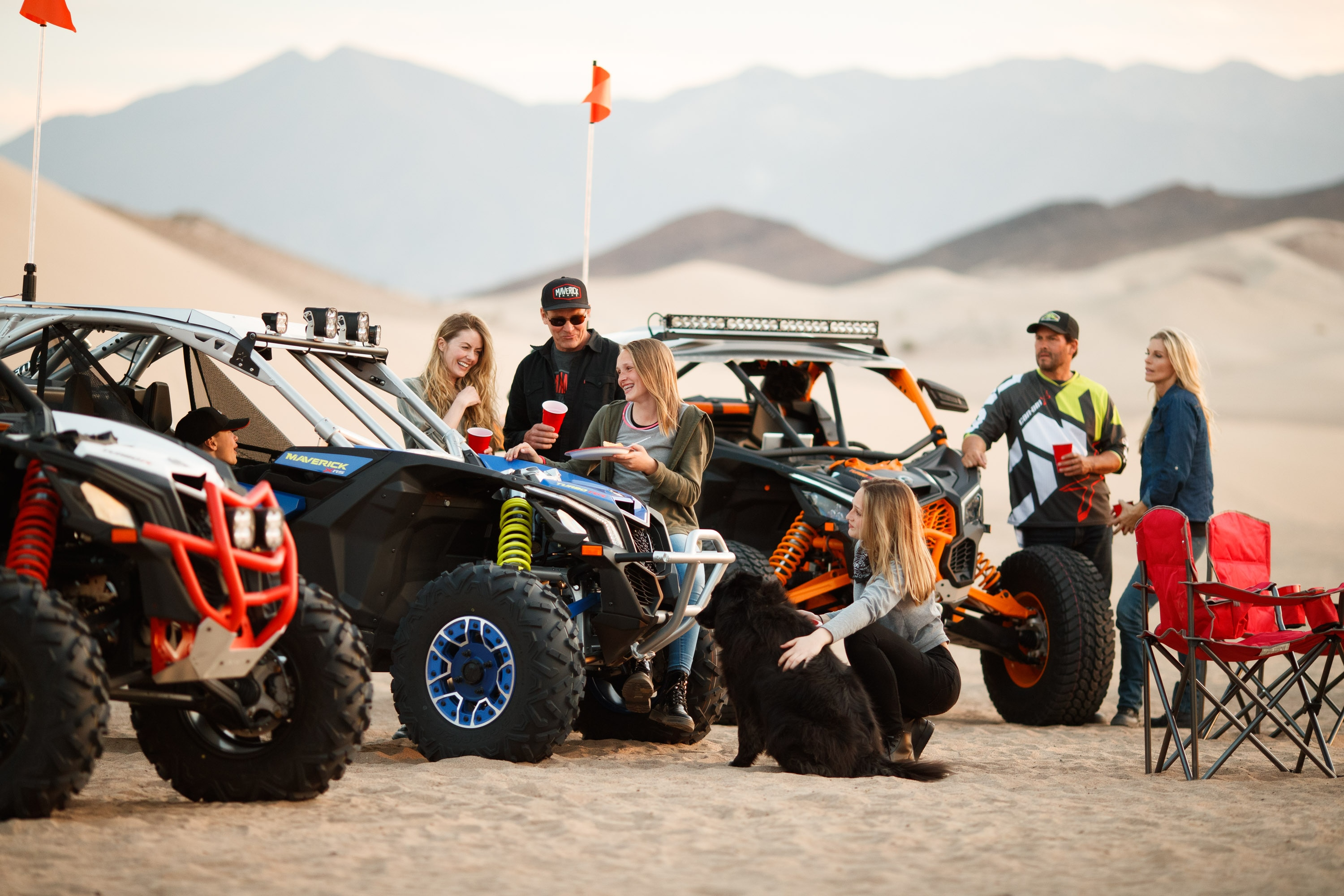 A bunch of people talking in the desert beside three 4-seater Can-Am Maverick X3 MAX side-by-side