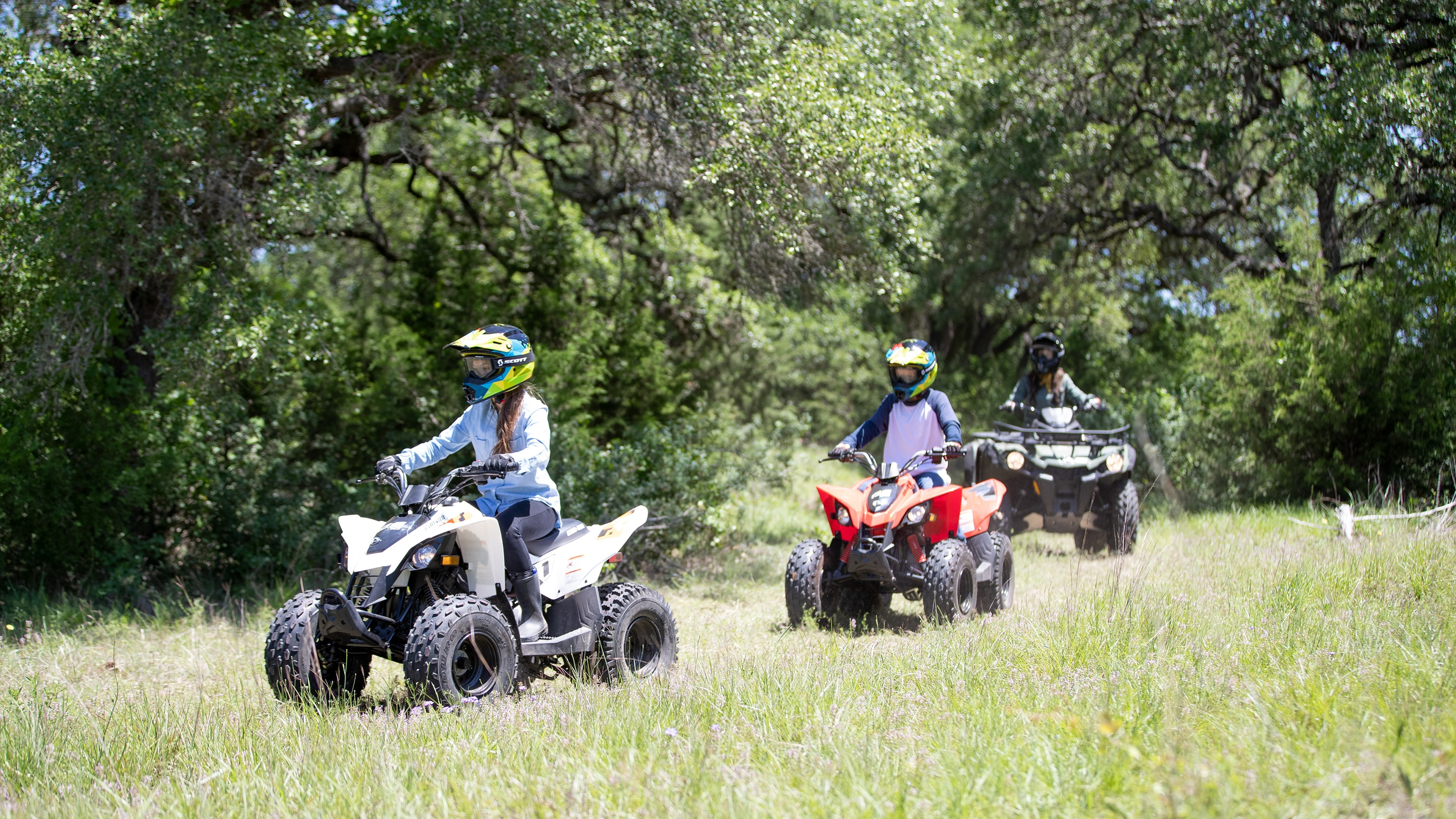 Two kids riding Can-Am DS ATVs and an adult in the background