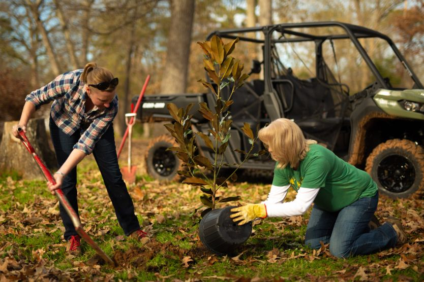 Two women from a non-profit organization planting tree and a Can-Am Defender in the back