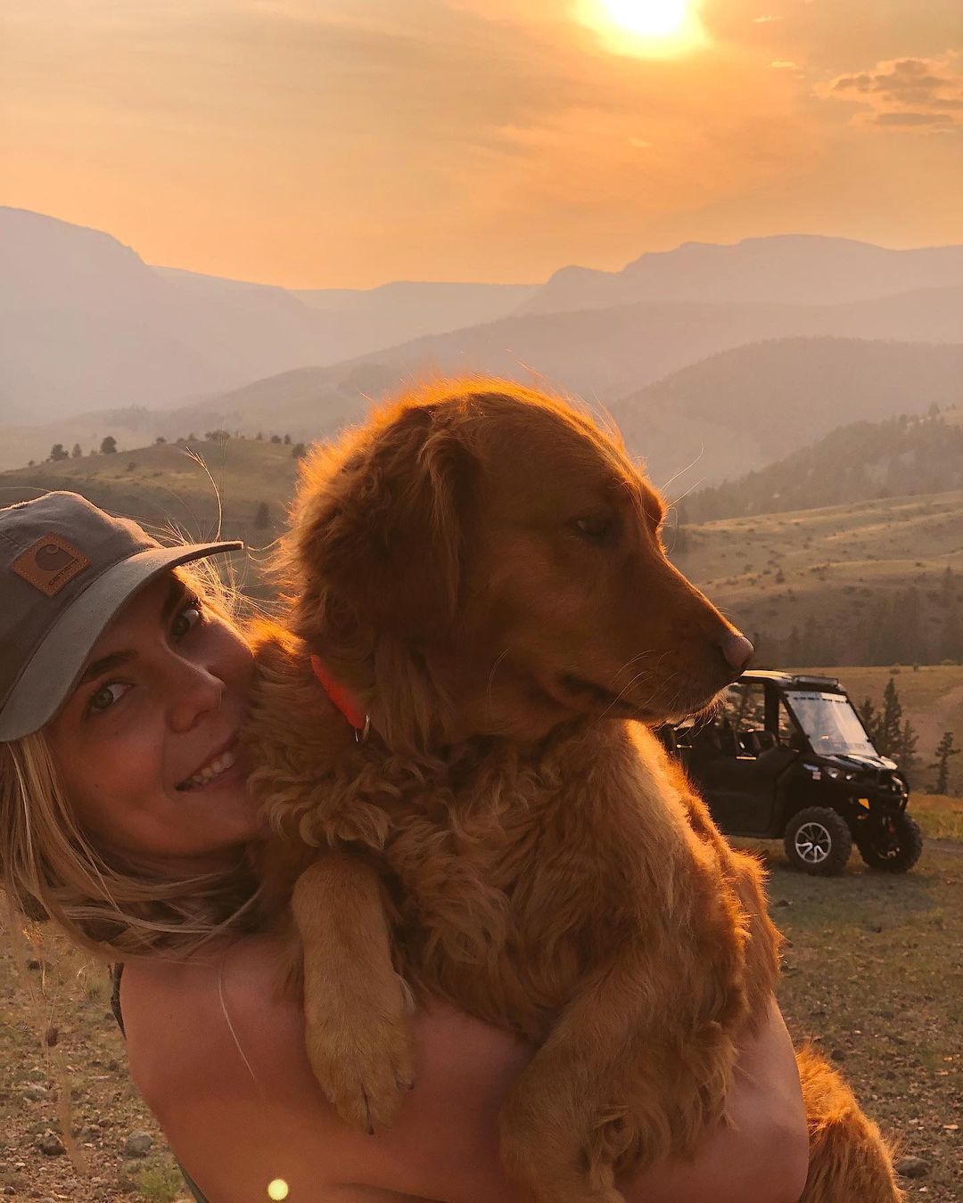 Claire Gierke hugging her dog with a Can-Am Defender Lone Star in the background