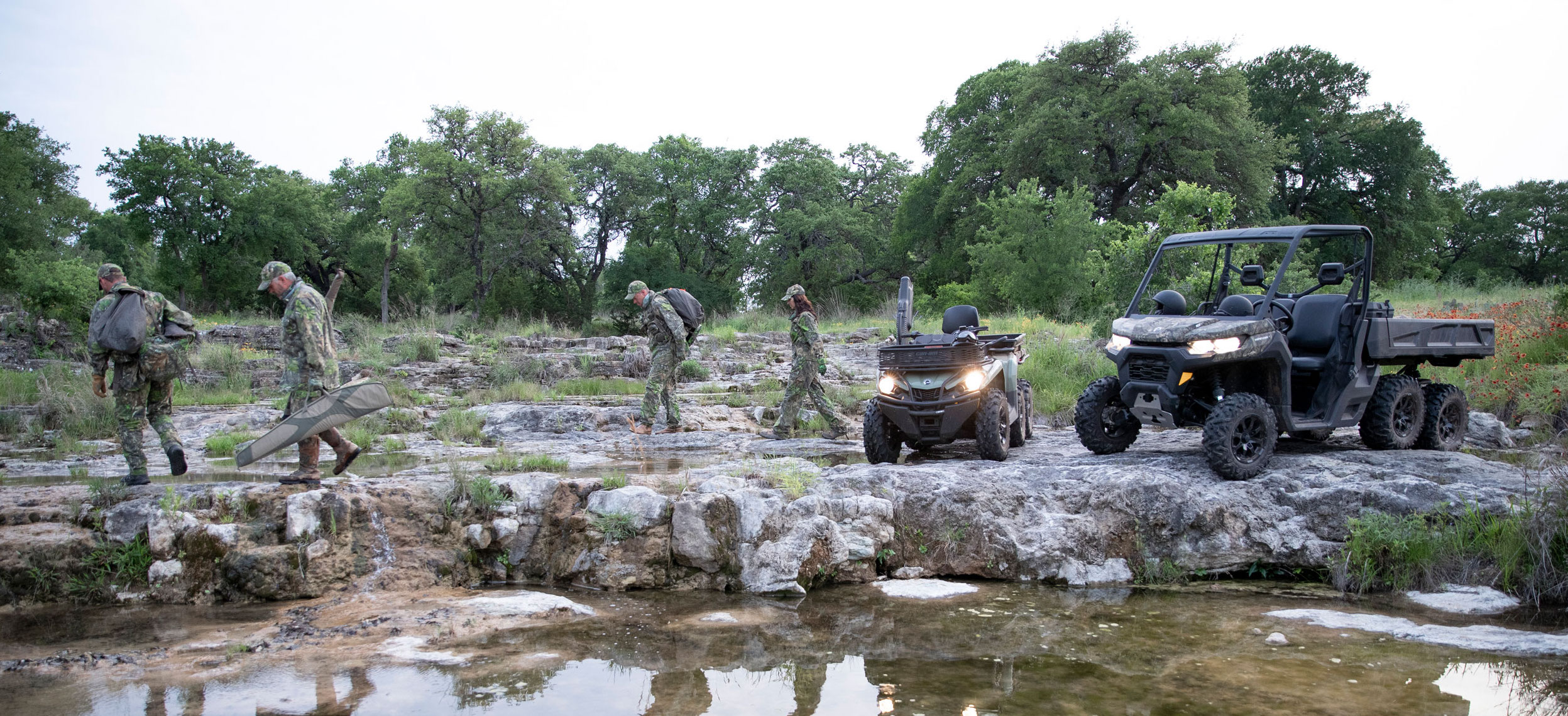 A group of hunters walking beside their Can-Am Outlander ATV and Can-Am Defender side-by-side