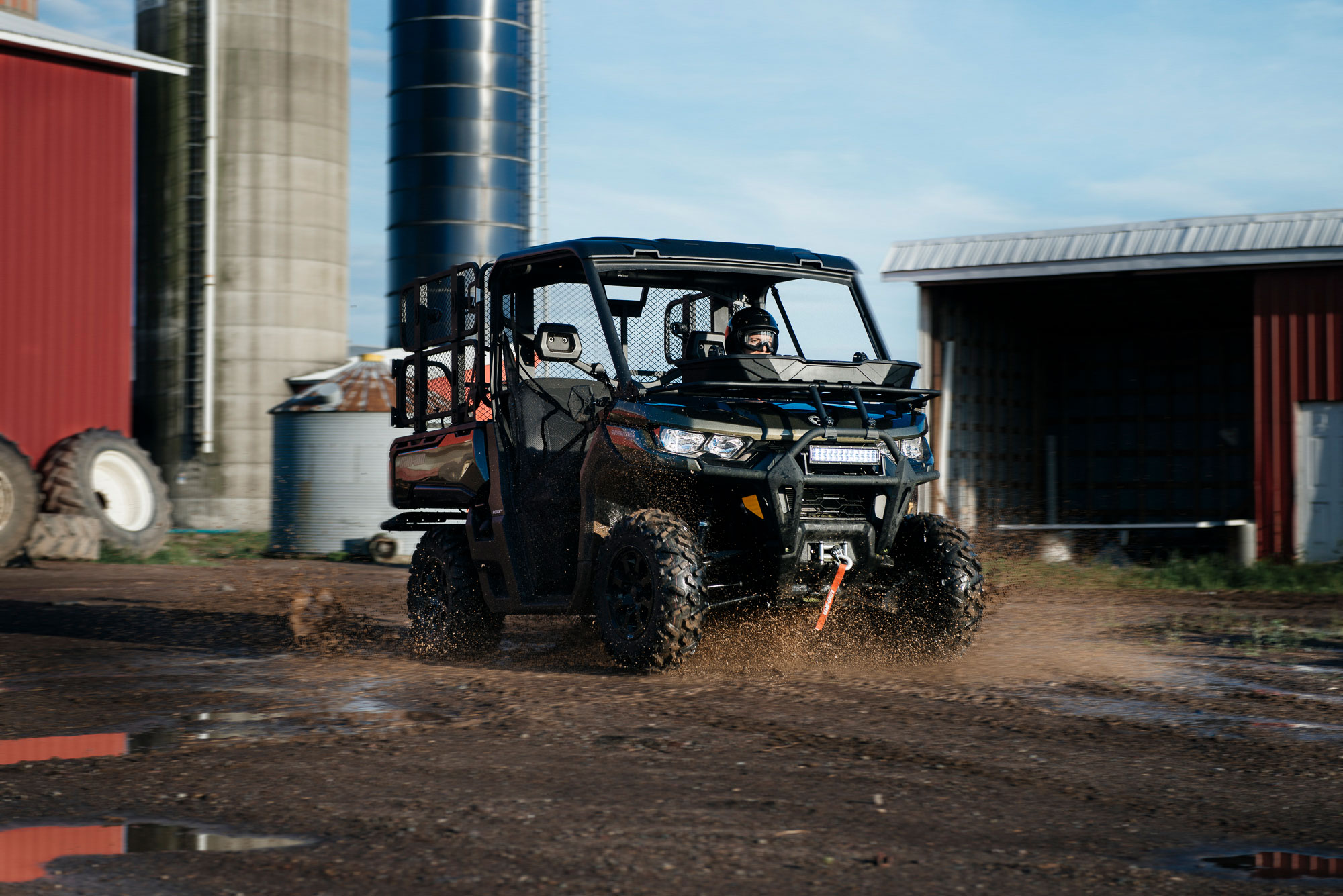 Man riding a custom Can-Am Defender side-by-side at the farm