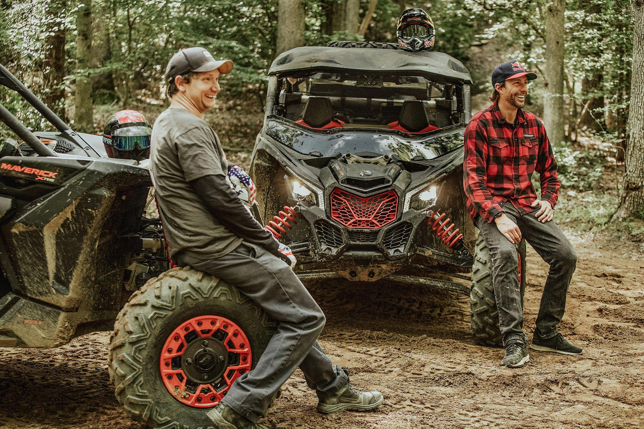 Two men sitting on the wheel of their Can-Am Maverick X3 laughing