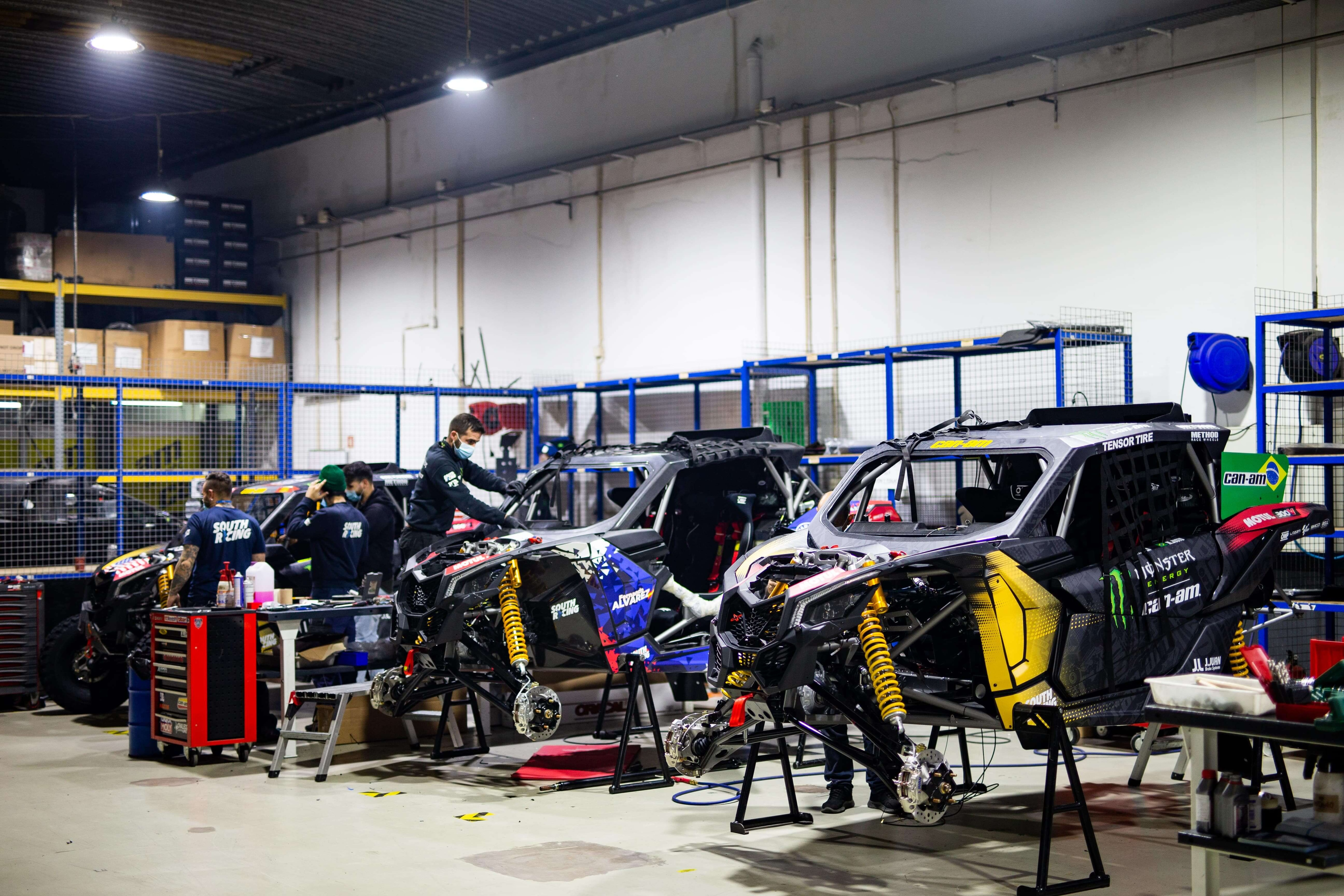 People preparing Can-Am Maverick X3 vehicles for 2021 Dakar Rally
