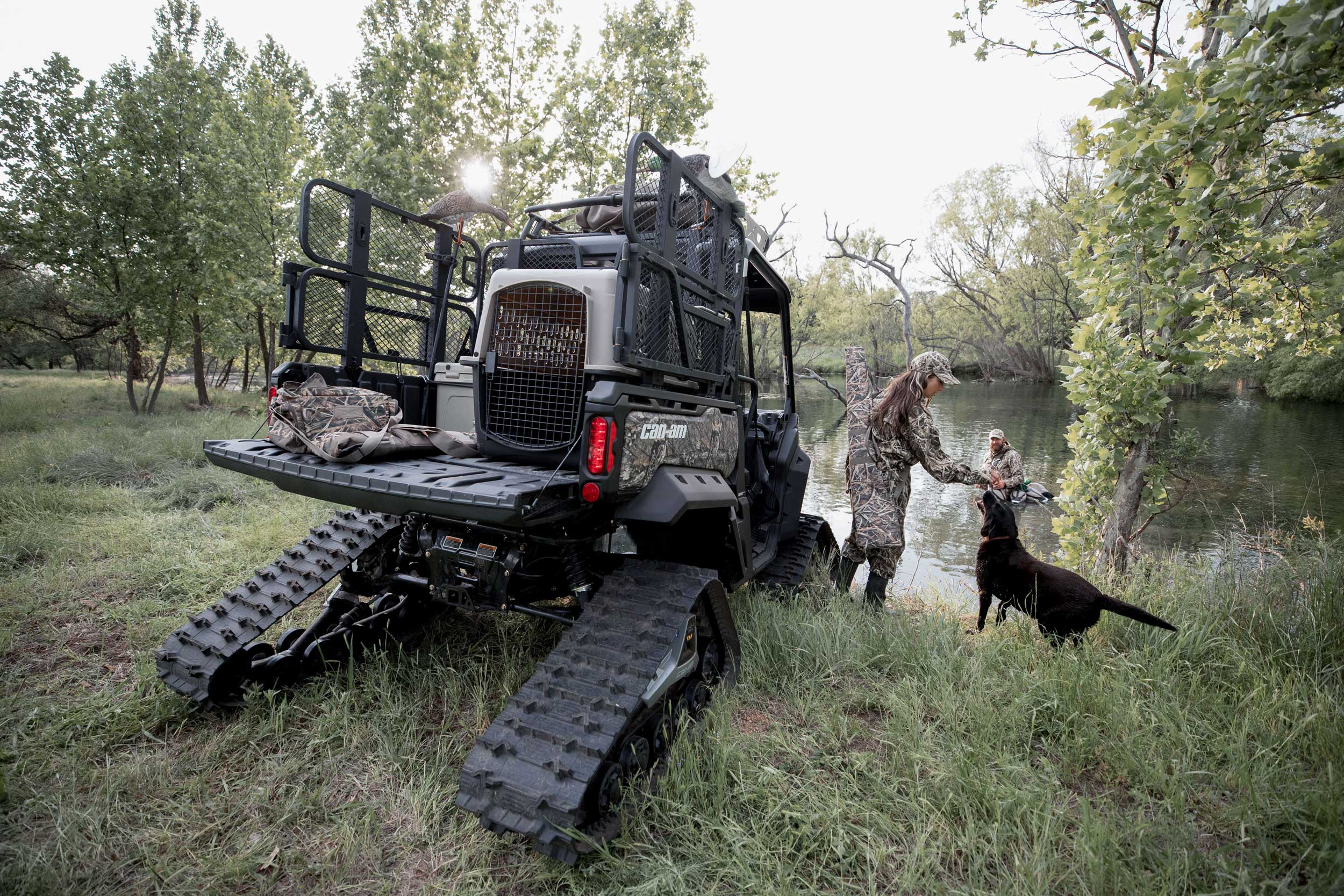 Rear view of a custom hunting Can-Am Defender and a couple and their dog