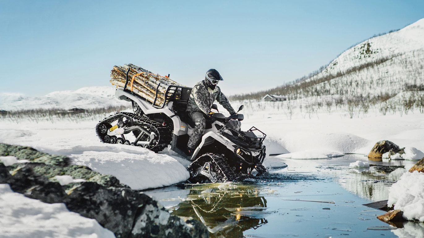 Man riding a custom Can-Am Outlander 6x6 ATV with Apache track kits in cold water