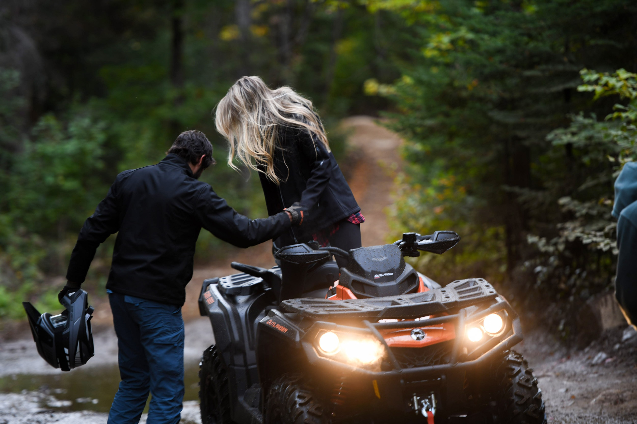 A man helping a woman to get out of a Can-Am Outlander MAX XT-P ATV