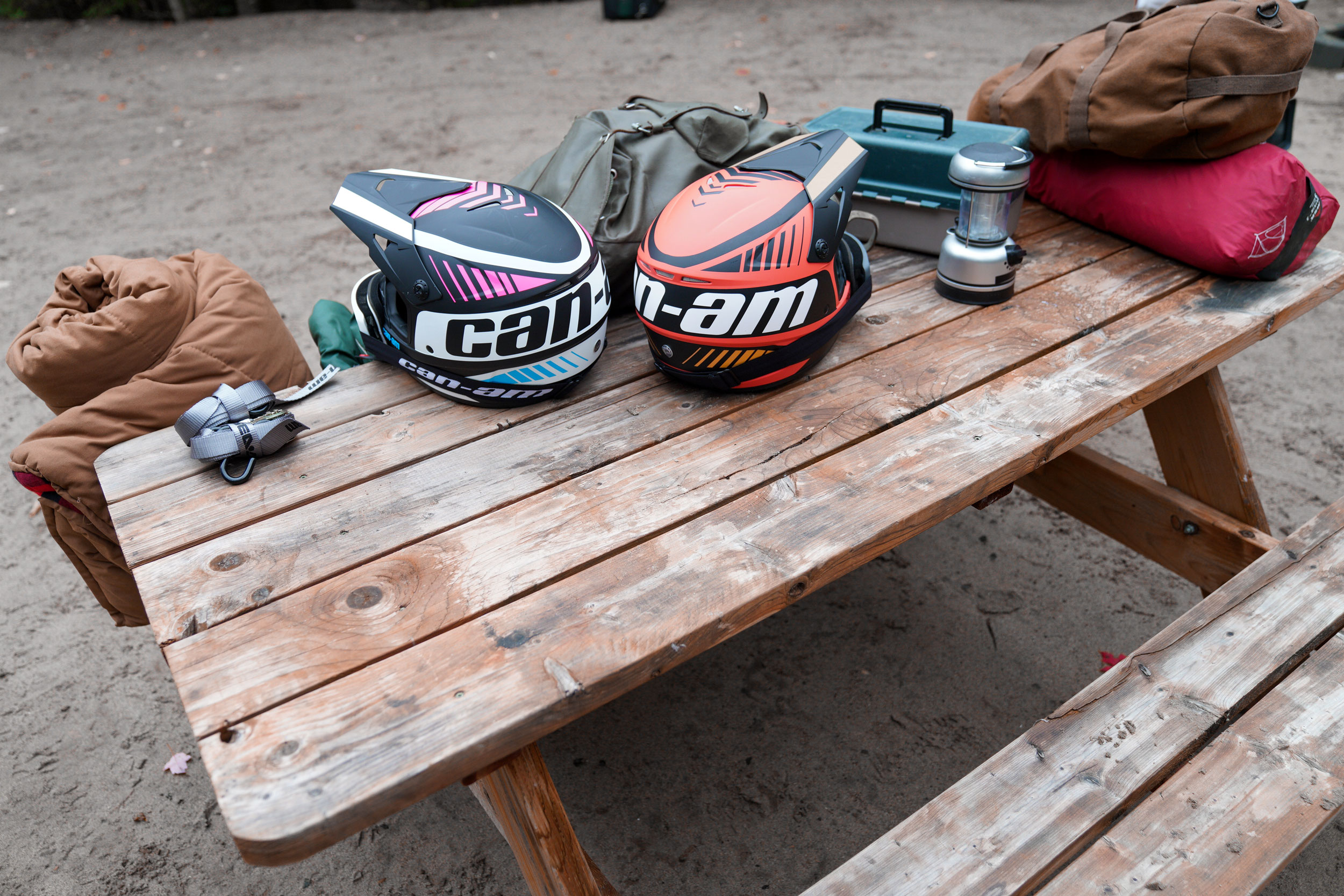 Two Can-Am Off-Road helmets with a bunch of camping accessories on a picnic table