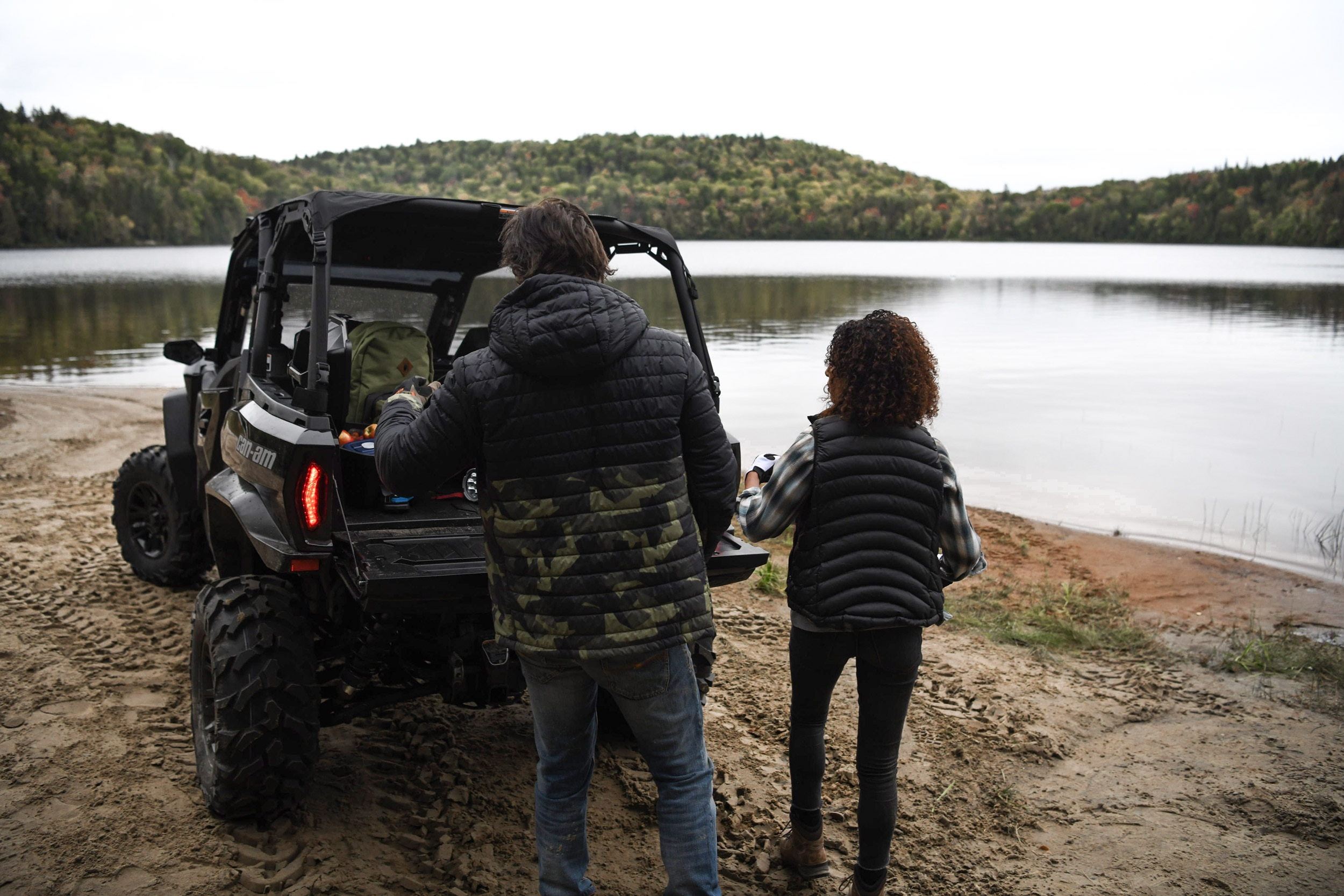 A man and a woman at the back of their 2021 Can-Am Commander near a small lake