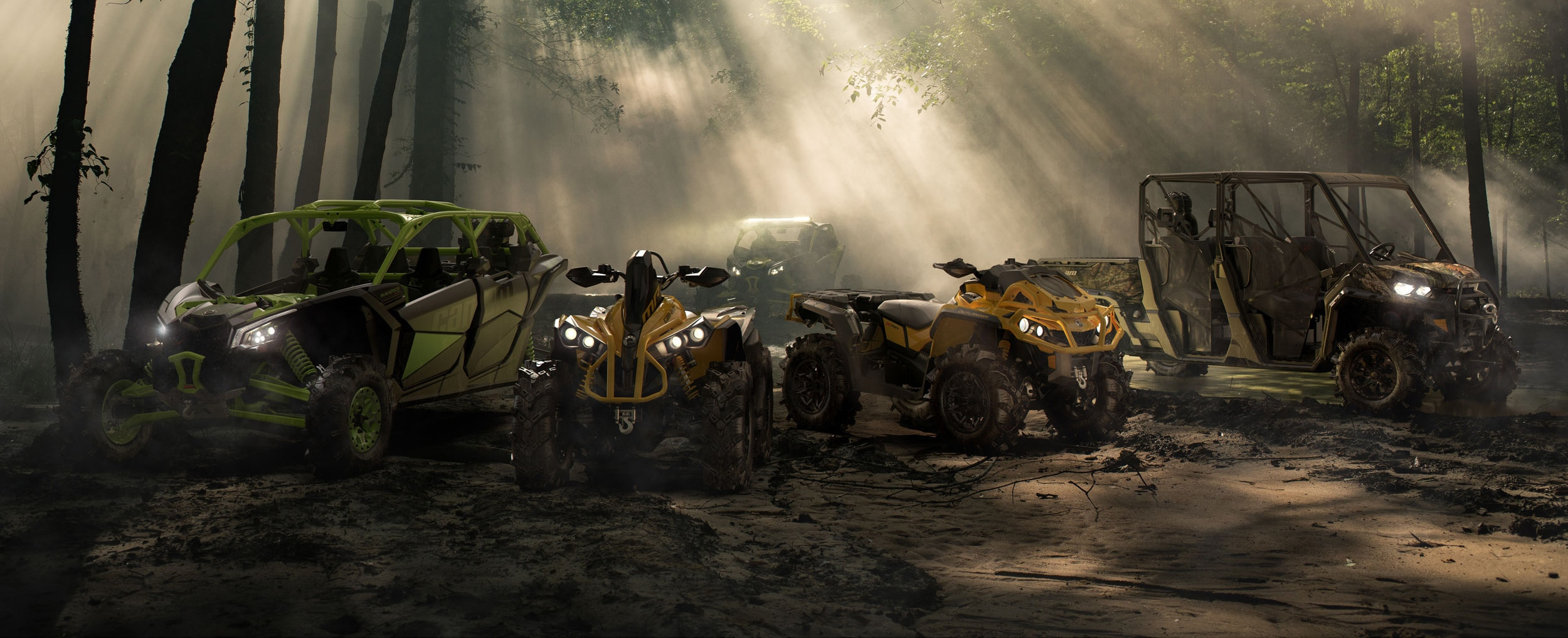 Two Can-Am ATVs and three Can-Am side-by-sides parked in a forest
