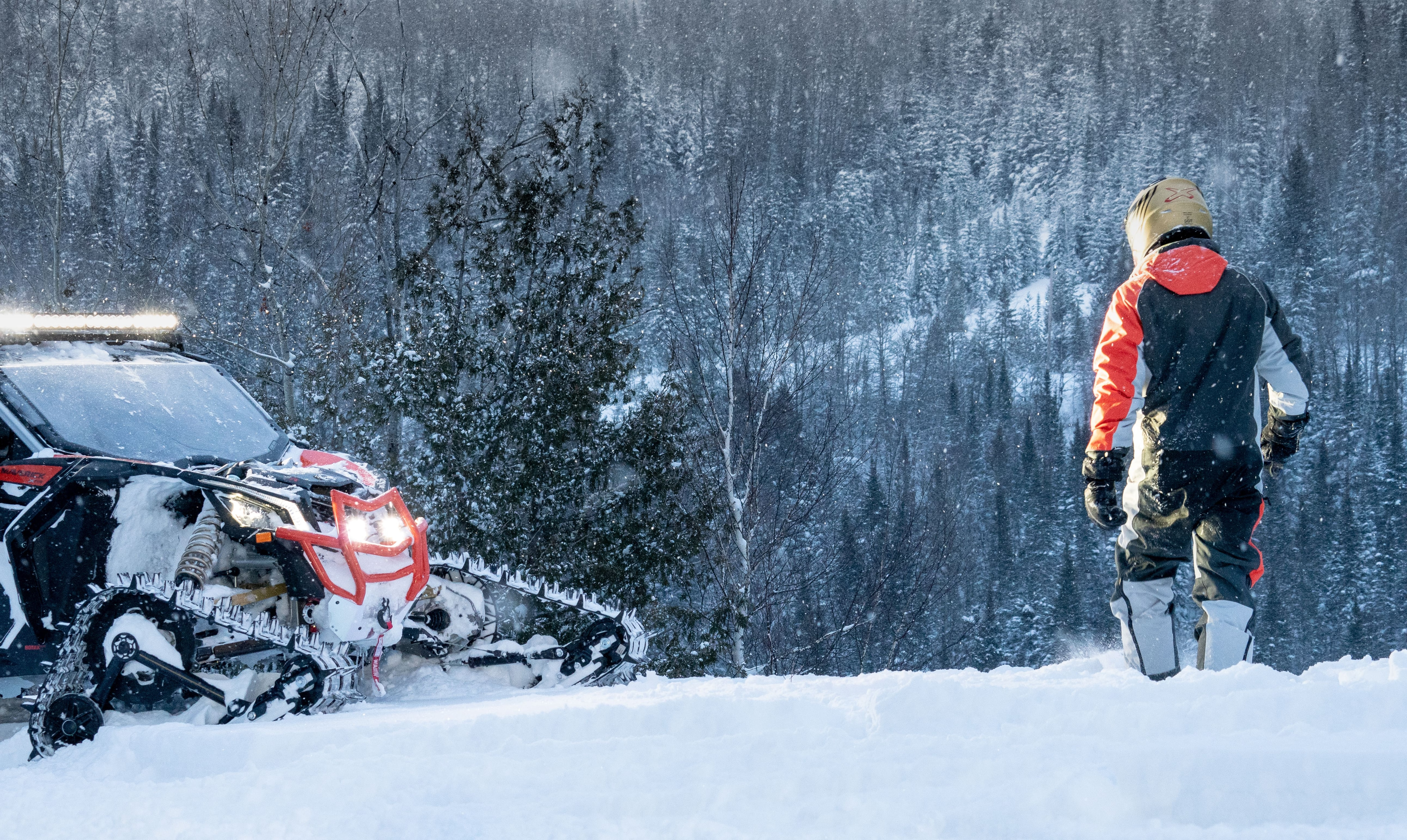 A rider in the snow with their side-by-side vehicle