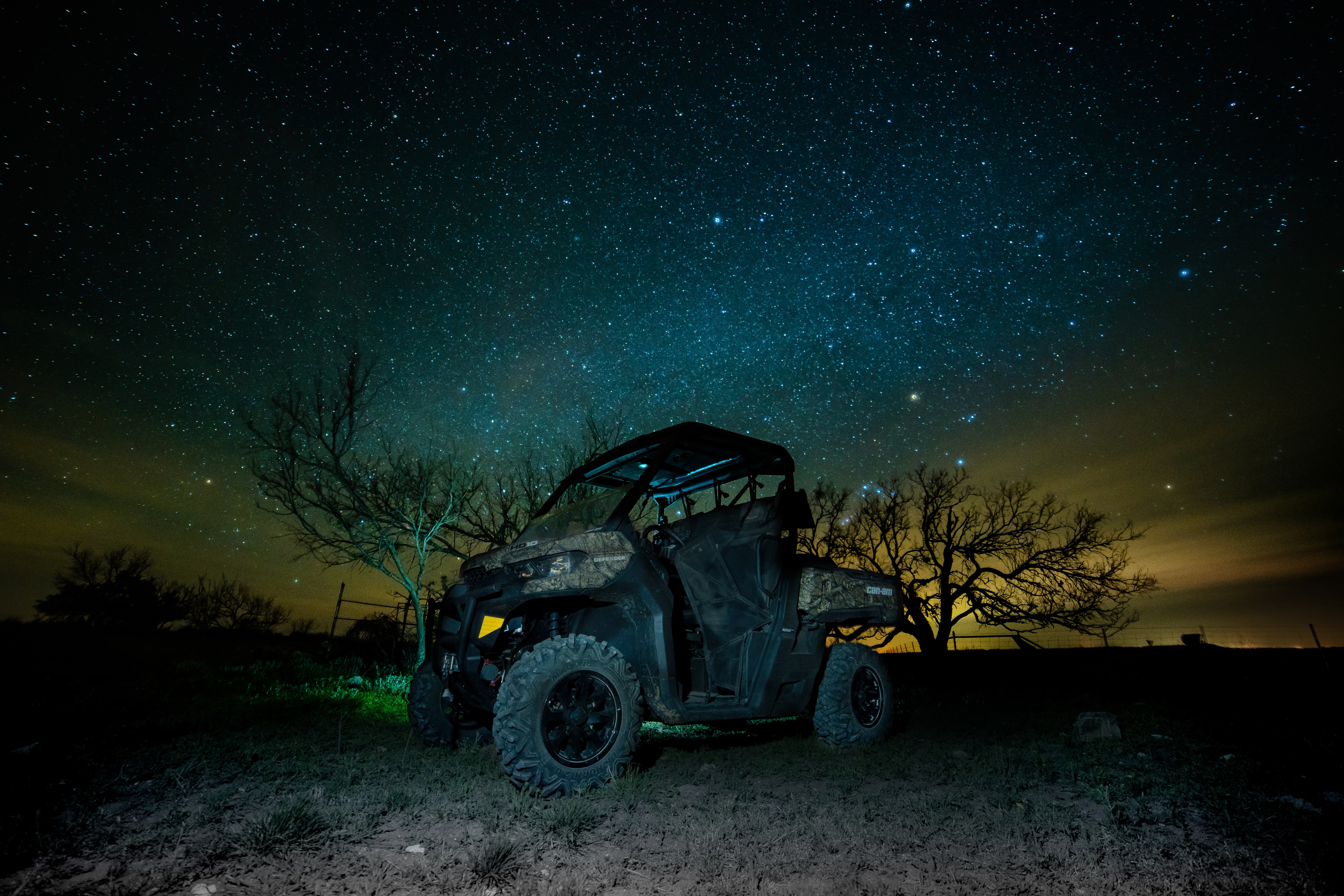 A parked Can-Am Defender Mossy Oak Edition in the dark with a starry sky