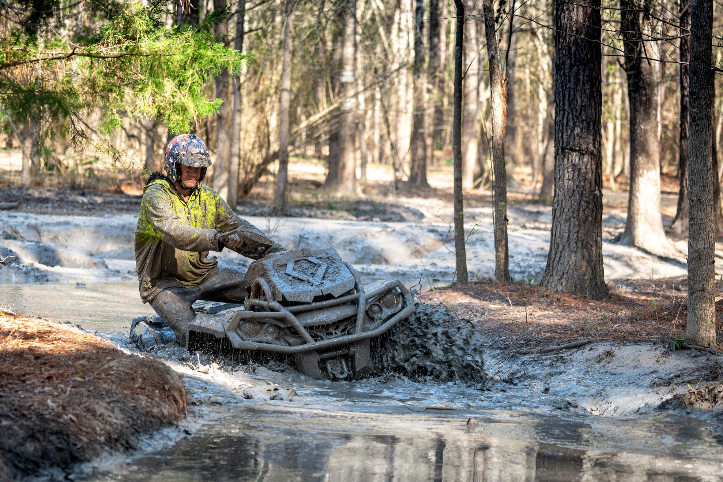 Dustin Jones riding a Can-Am Outlander X mr ATV deep in a mud trail
