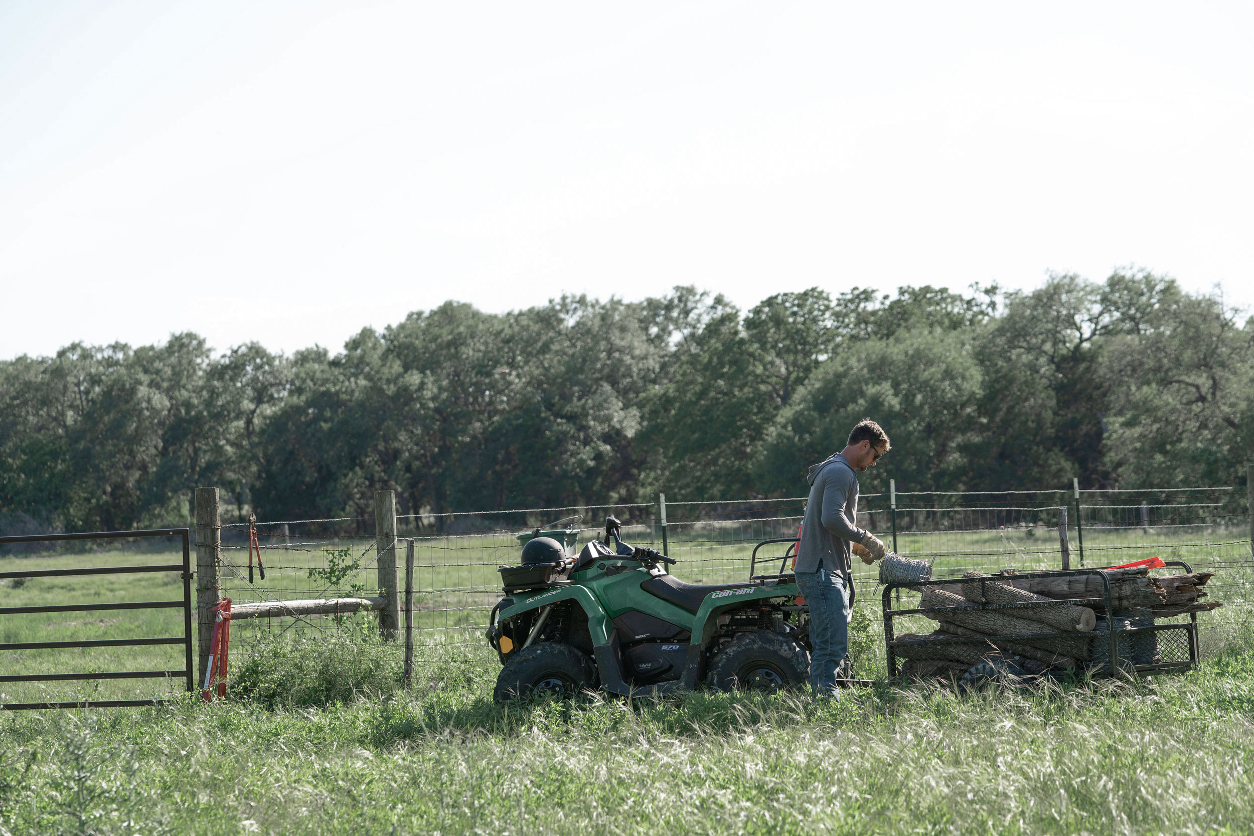 A Can-Am Outlander ATV and a man feeding cattle