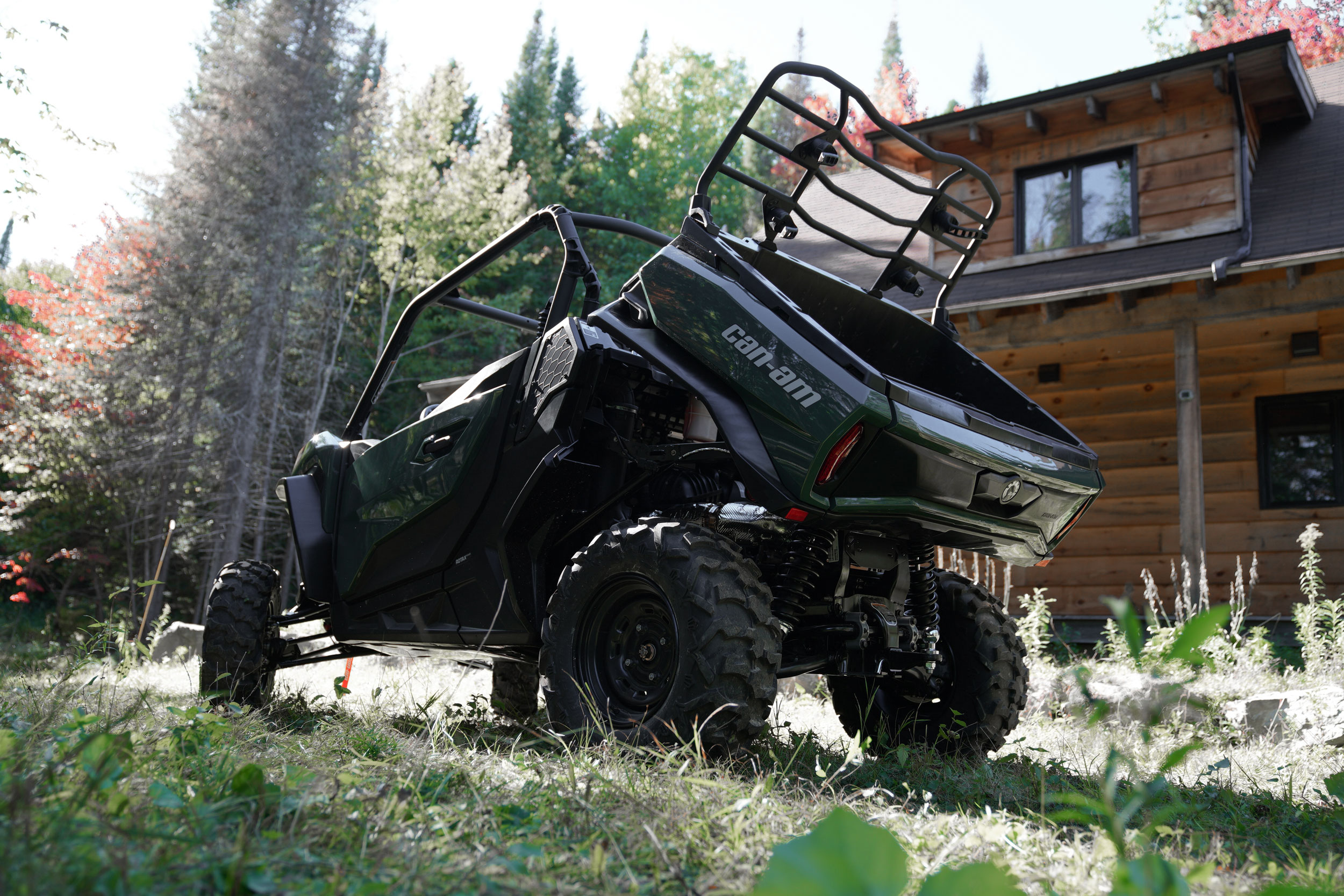 A 2021 Can-Am Commander with a tilt bed near a wooden chalet