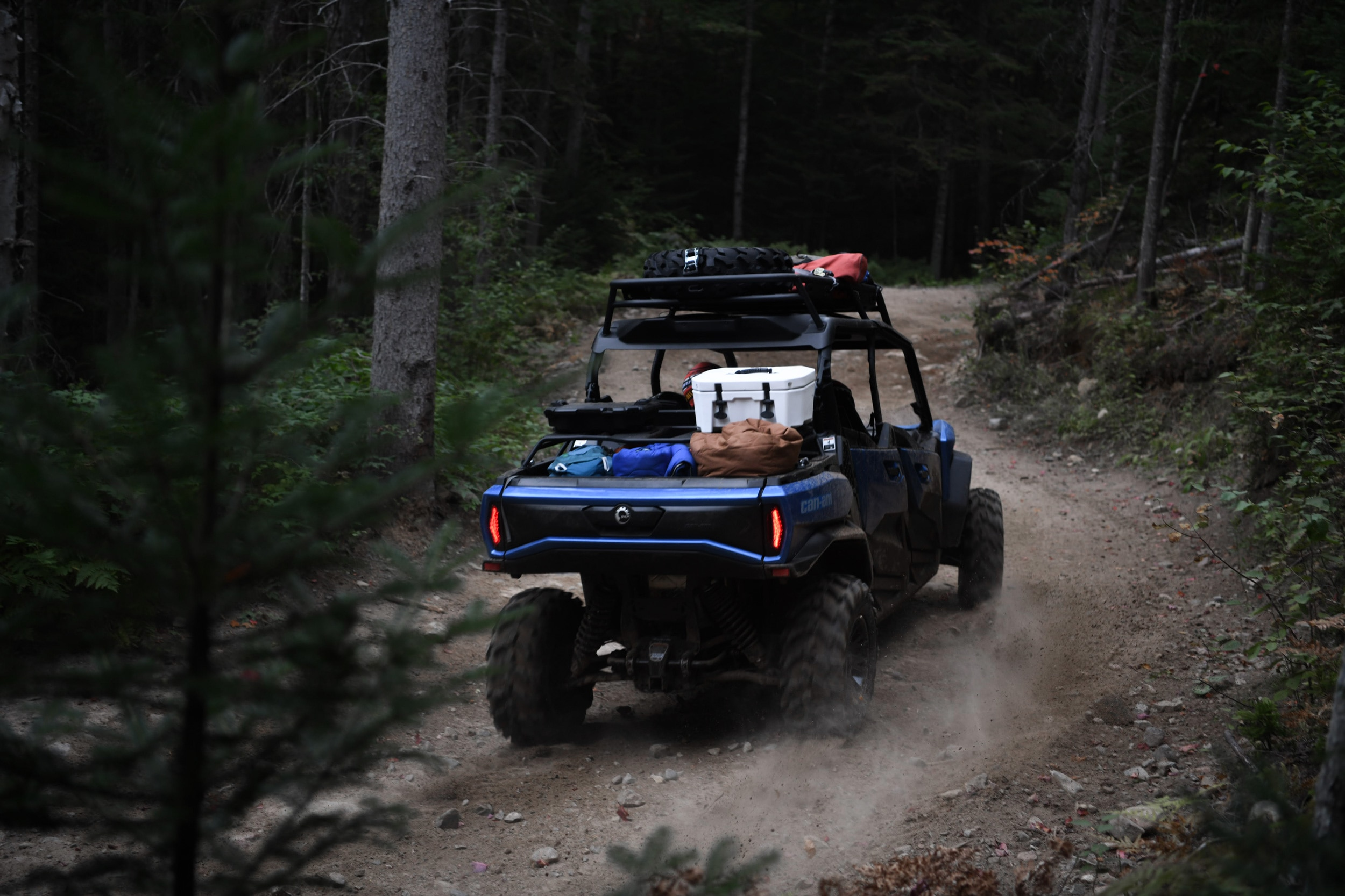 Two people riding a 2021 Can-Am Commander MAX XT in a trail