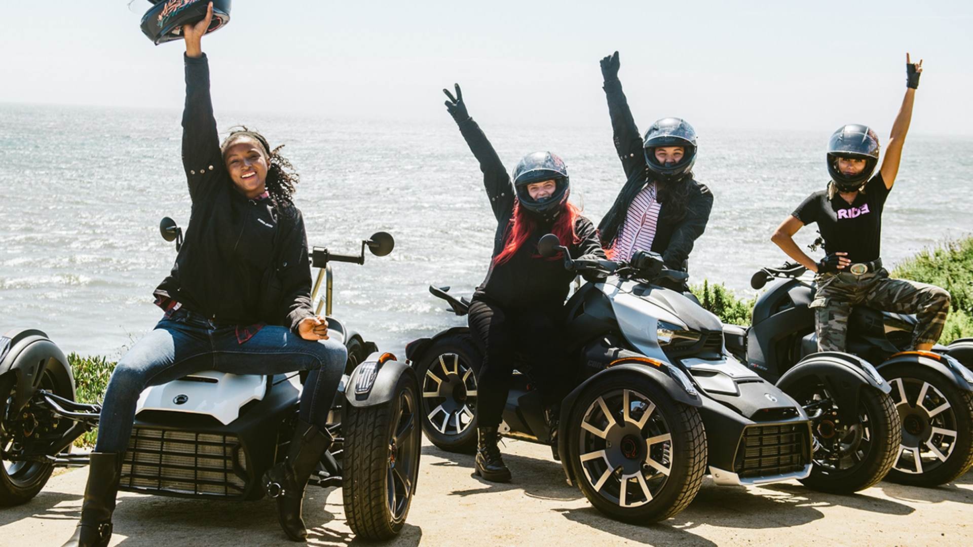 Women sitting on their Can-Am Ryker and raising their arm in the sky