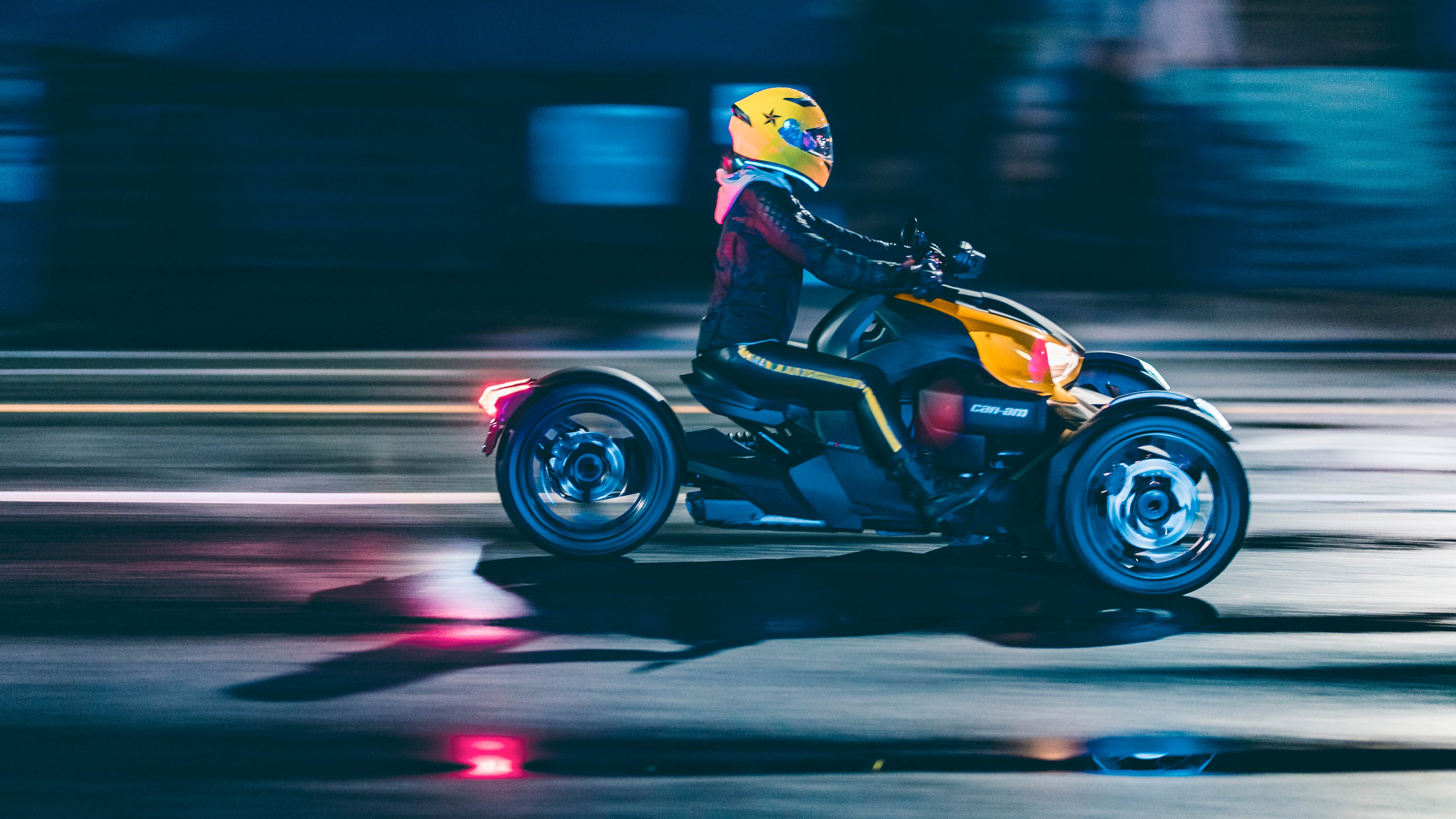 Woman riding Can-Am Ryker vehicle with yellow helmet