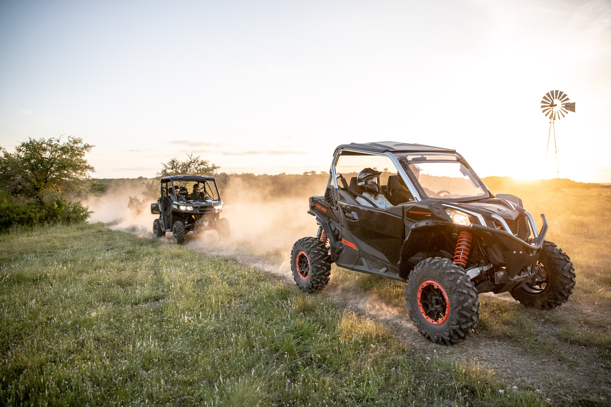Group riding Can-Am Maverick vehicles in a trail at sunset