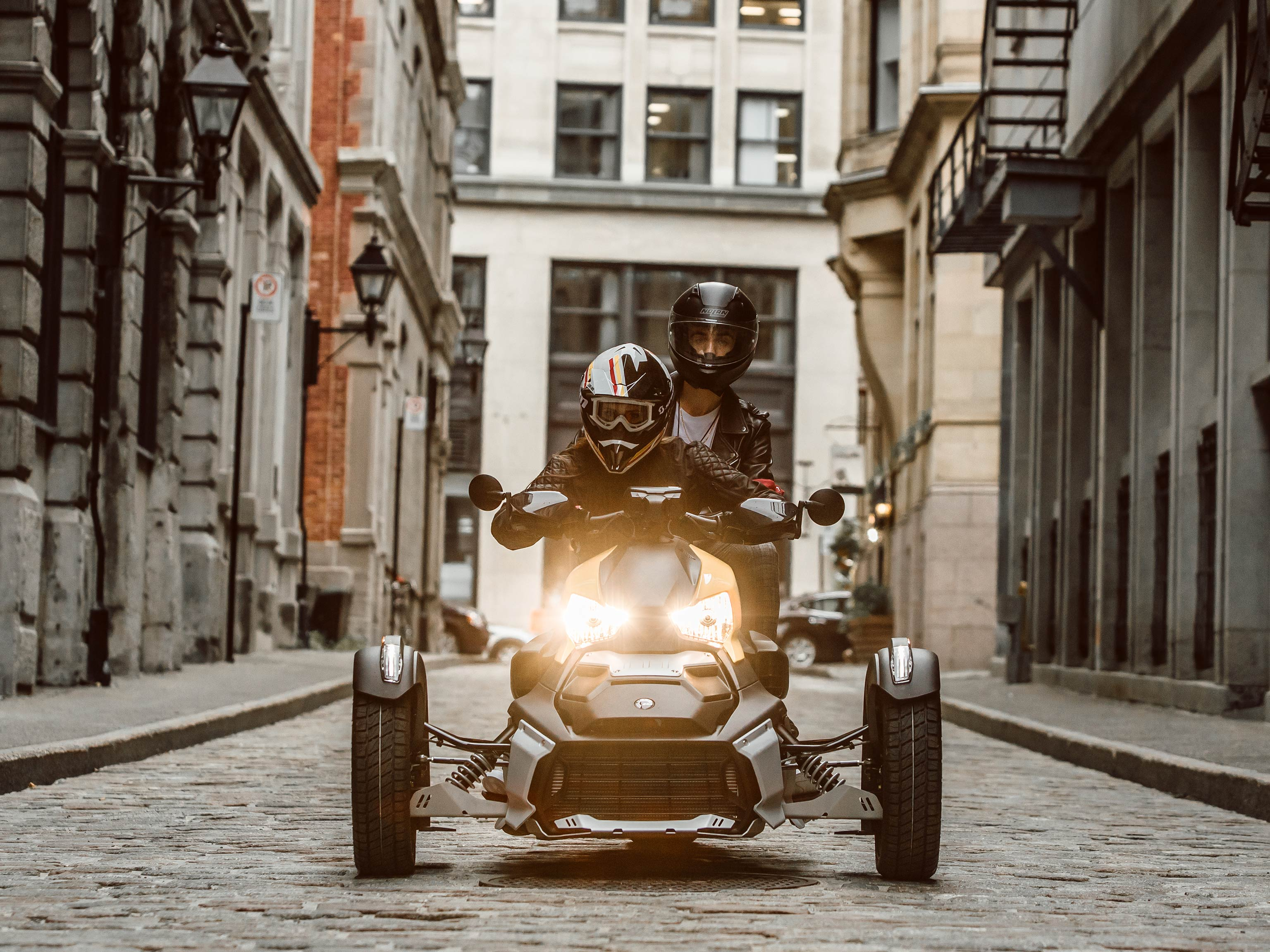 A couple riding a Can-Am vehicle along a narrow cobblestone street