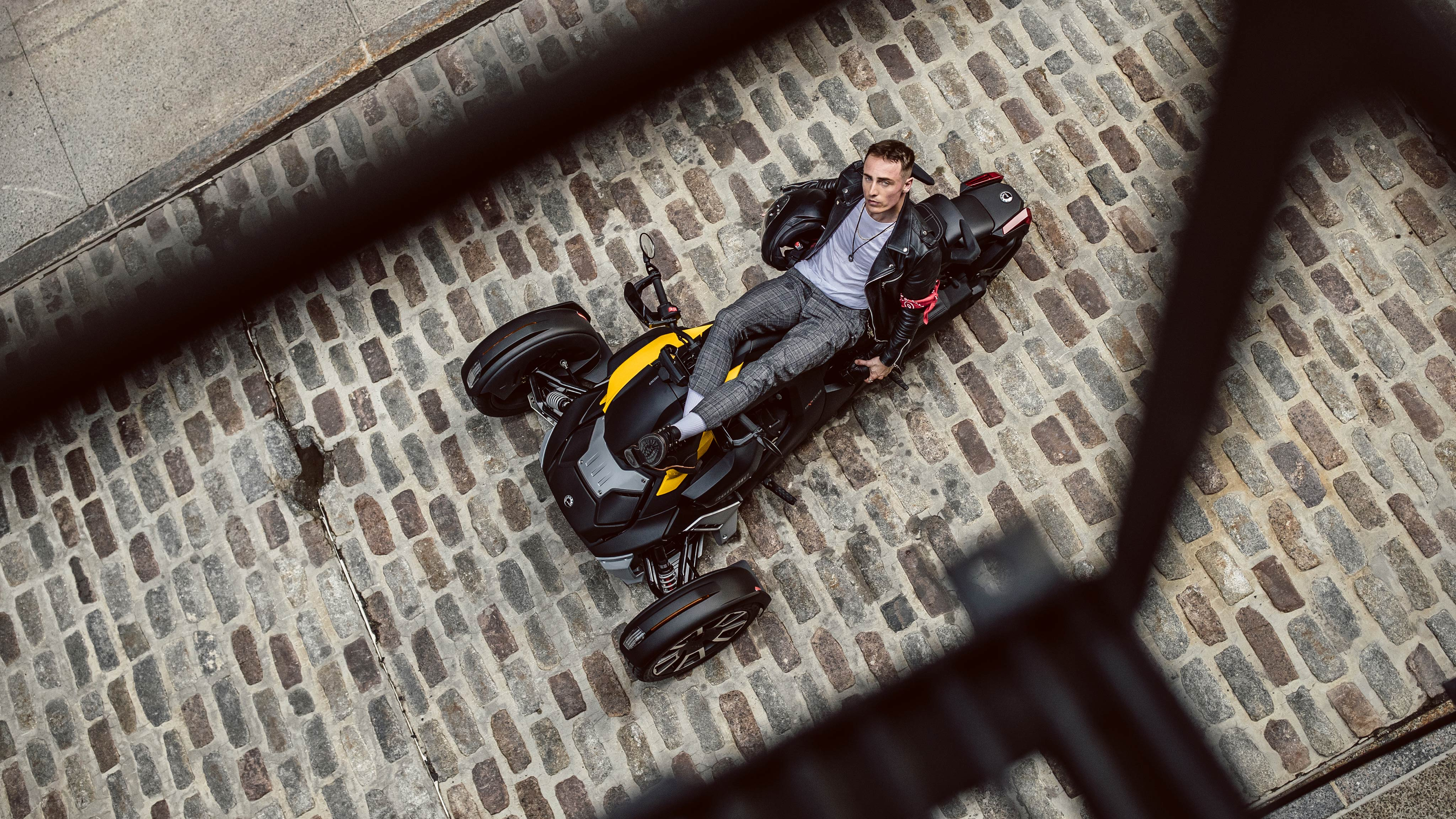 A man reclining on his Can-Am vehicle, which is parked in a cobblestone alleyway