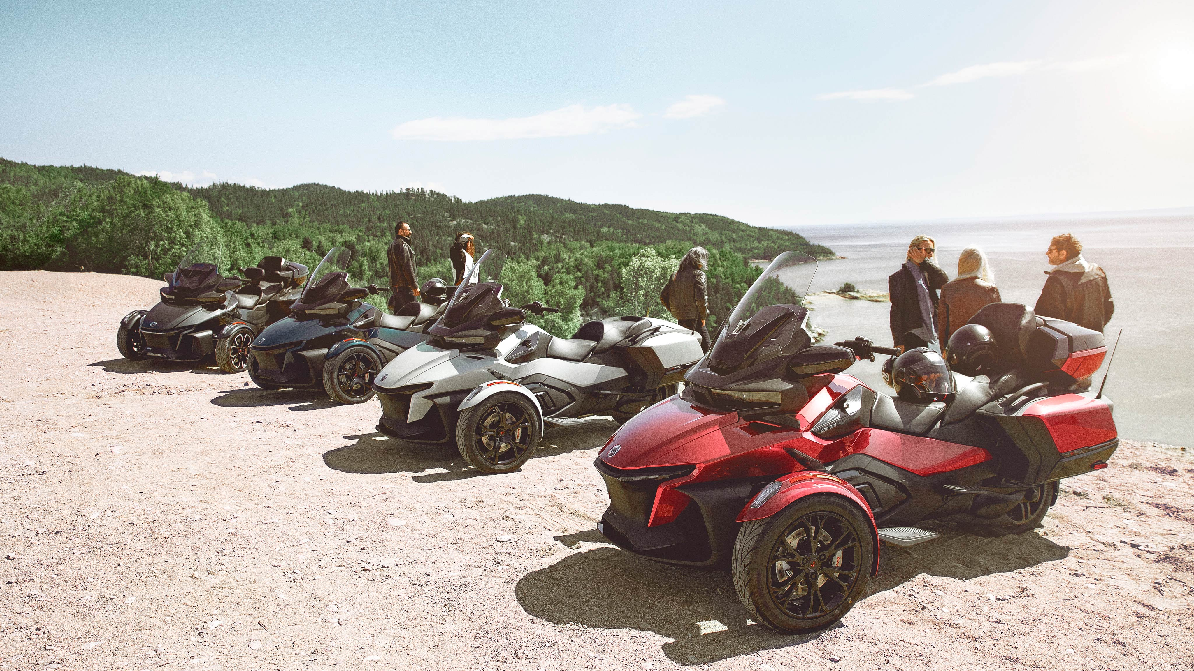 People chatting around 4 2020 Can-Am Spyder RT models, in front of a cliff
