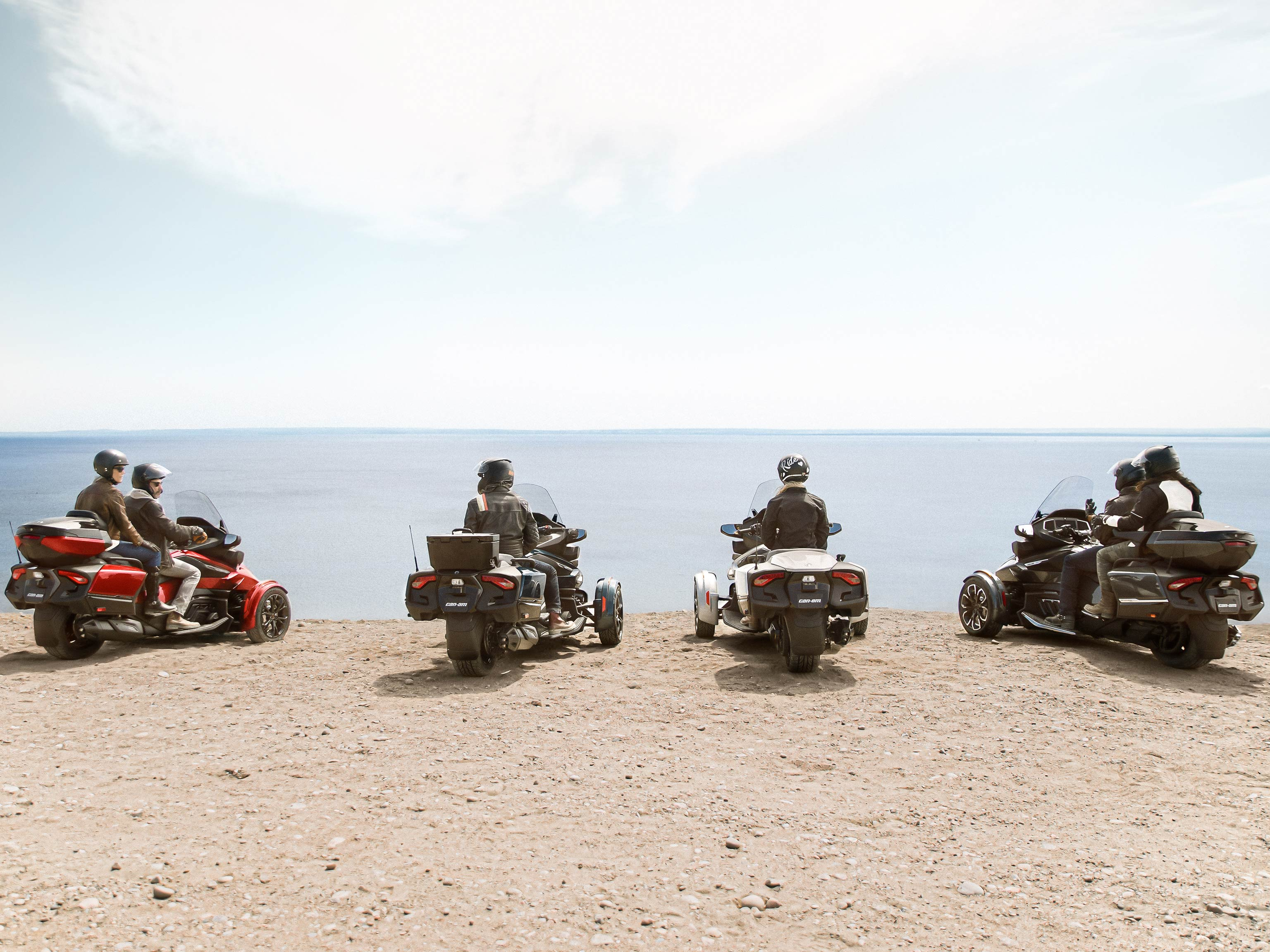 A group of friends admiring the open water while sitting on their Can-Am vehicles
