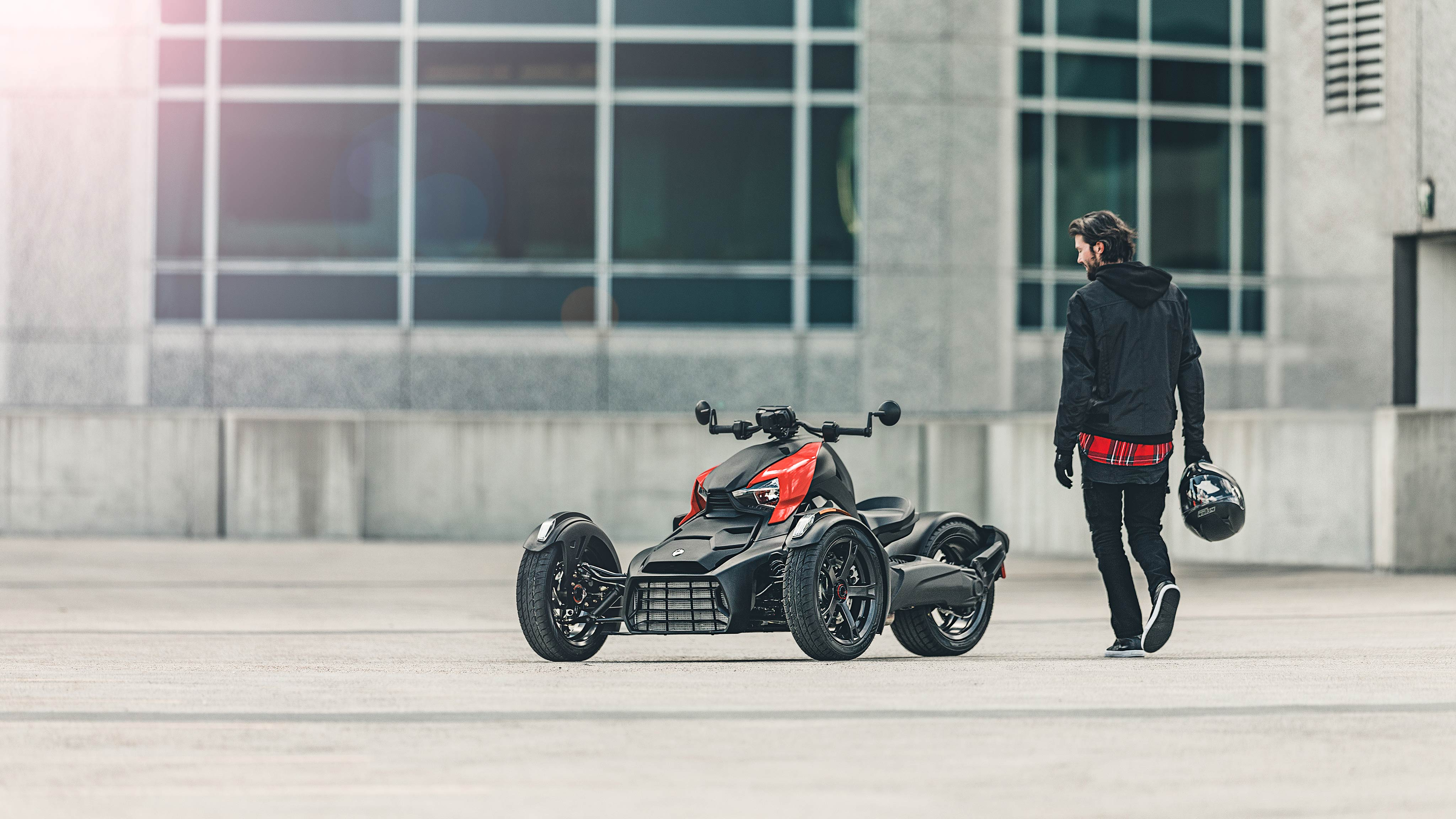 A man, helmet in hand, walking toward his Can-Am vehicle with Adrenaline Red panels parked in an empty concrete lot