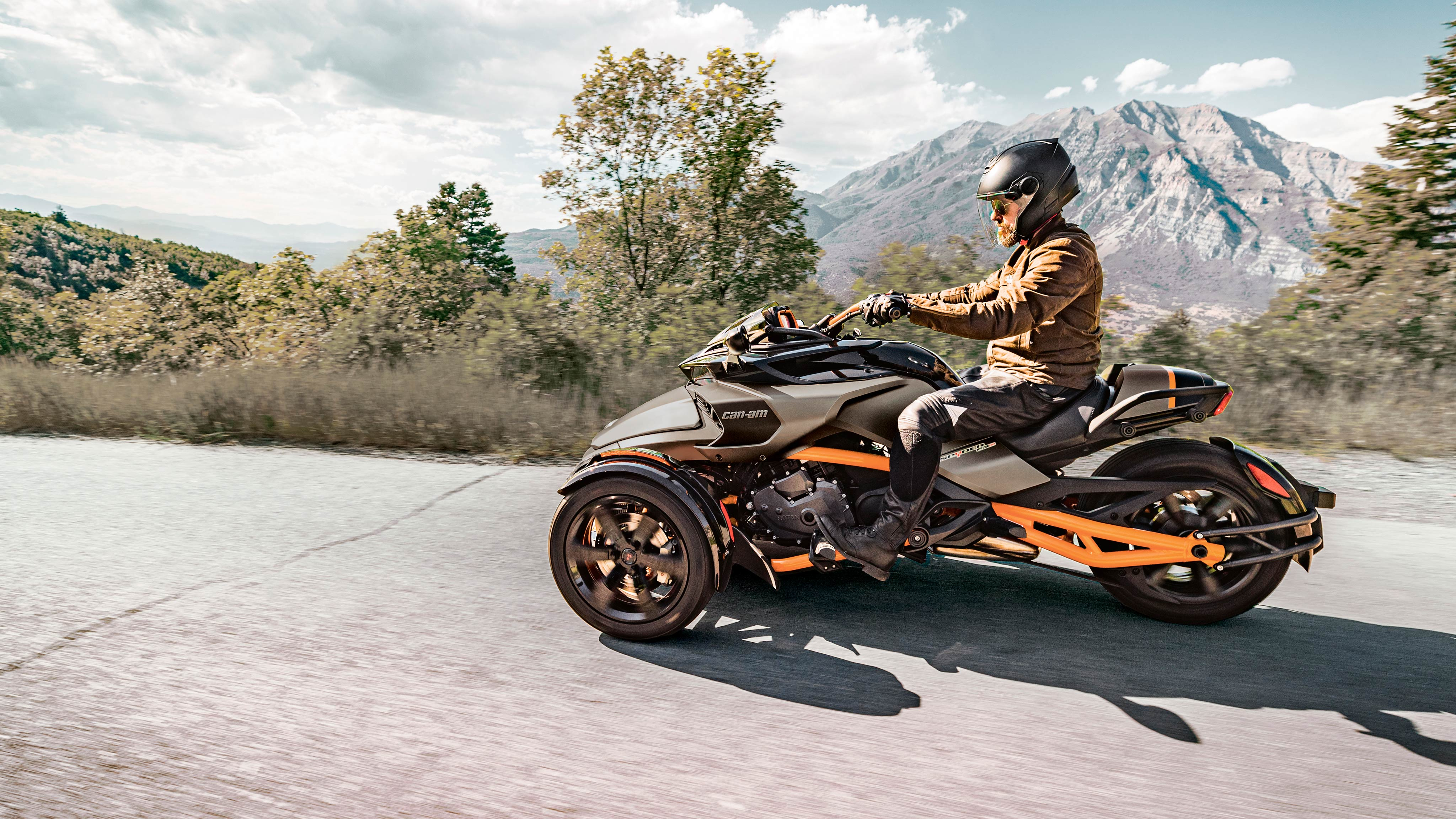 A man riding his Can-Am Spyder along the open road in front of a mountainous landscape