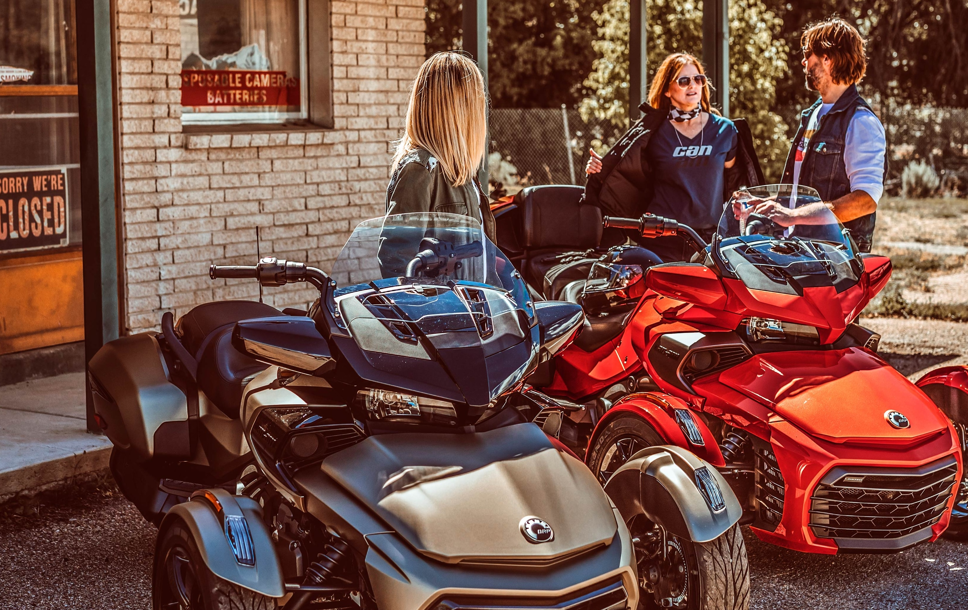 Three friends chatting by two Can-Am Spyder vehicles parked in front of a general store