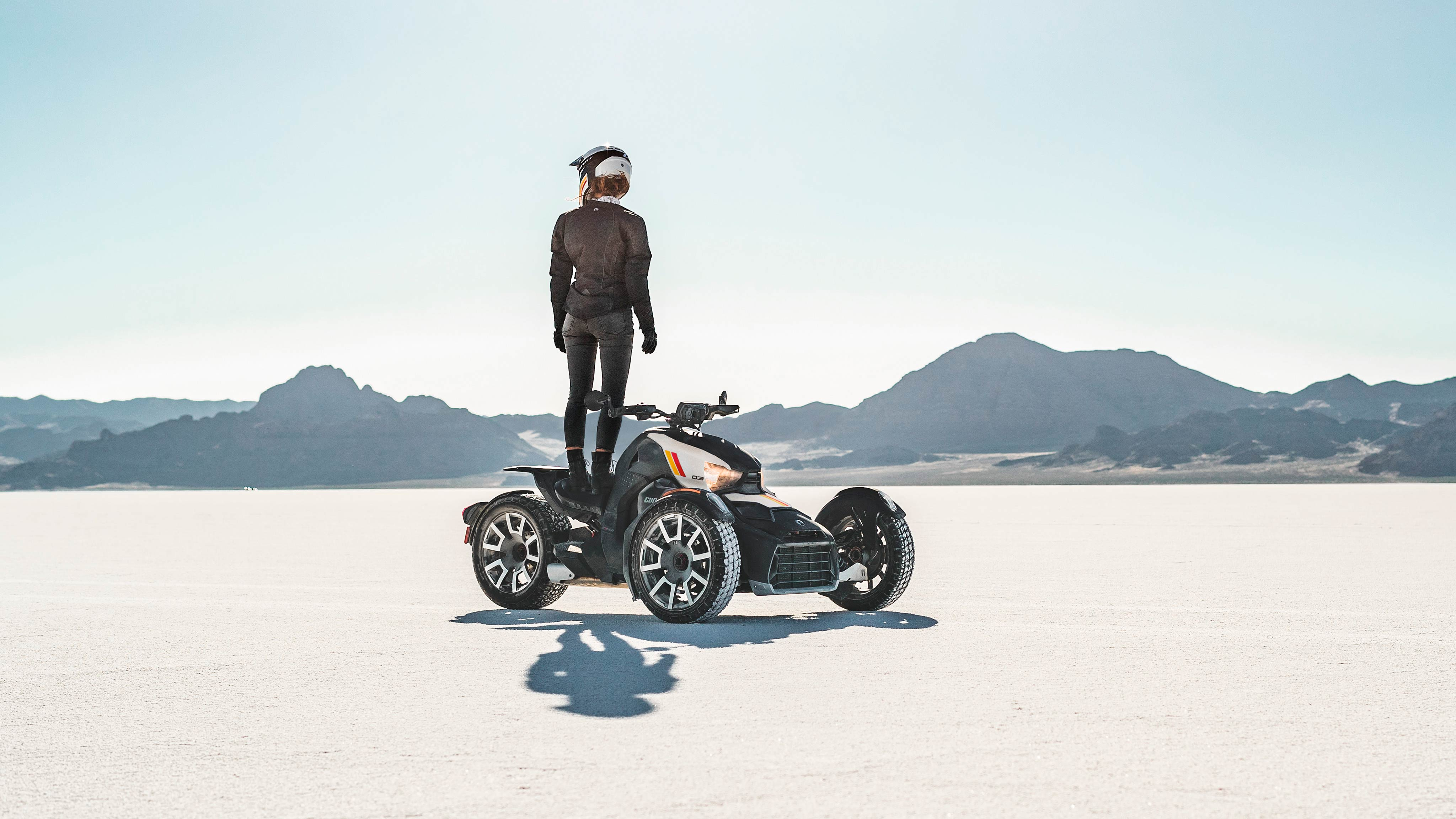 A man standing on his Can-Am vehicle contemplating the desert landscape.