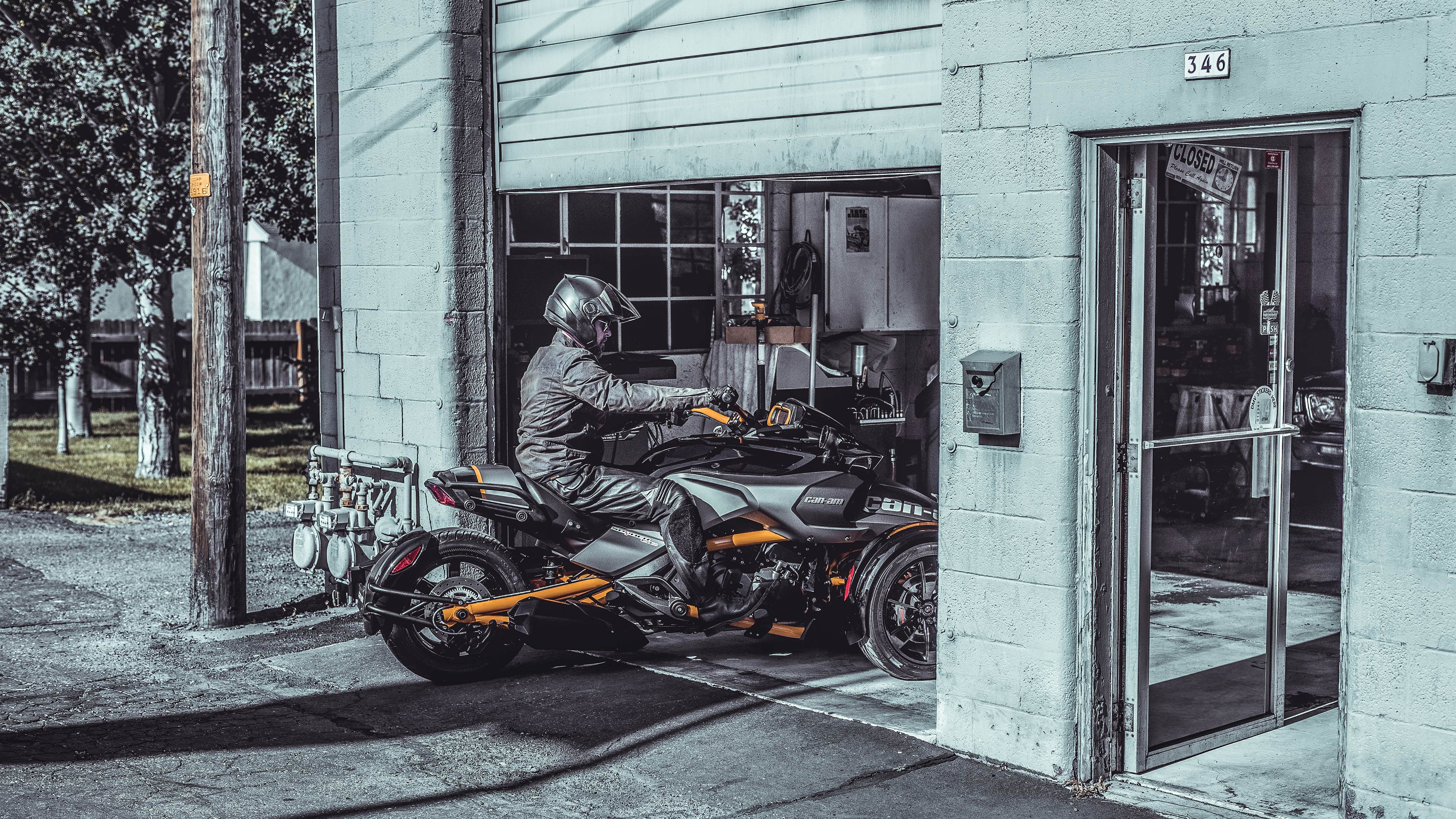 A man driving his Can-Am vehicle into a garage