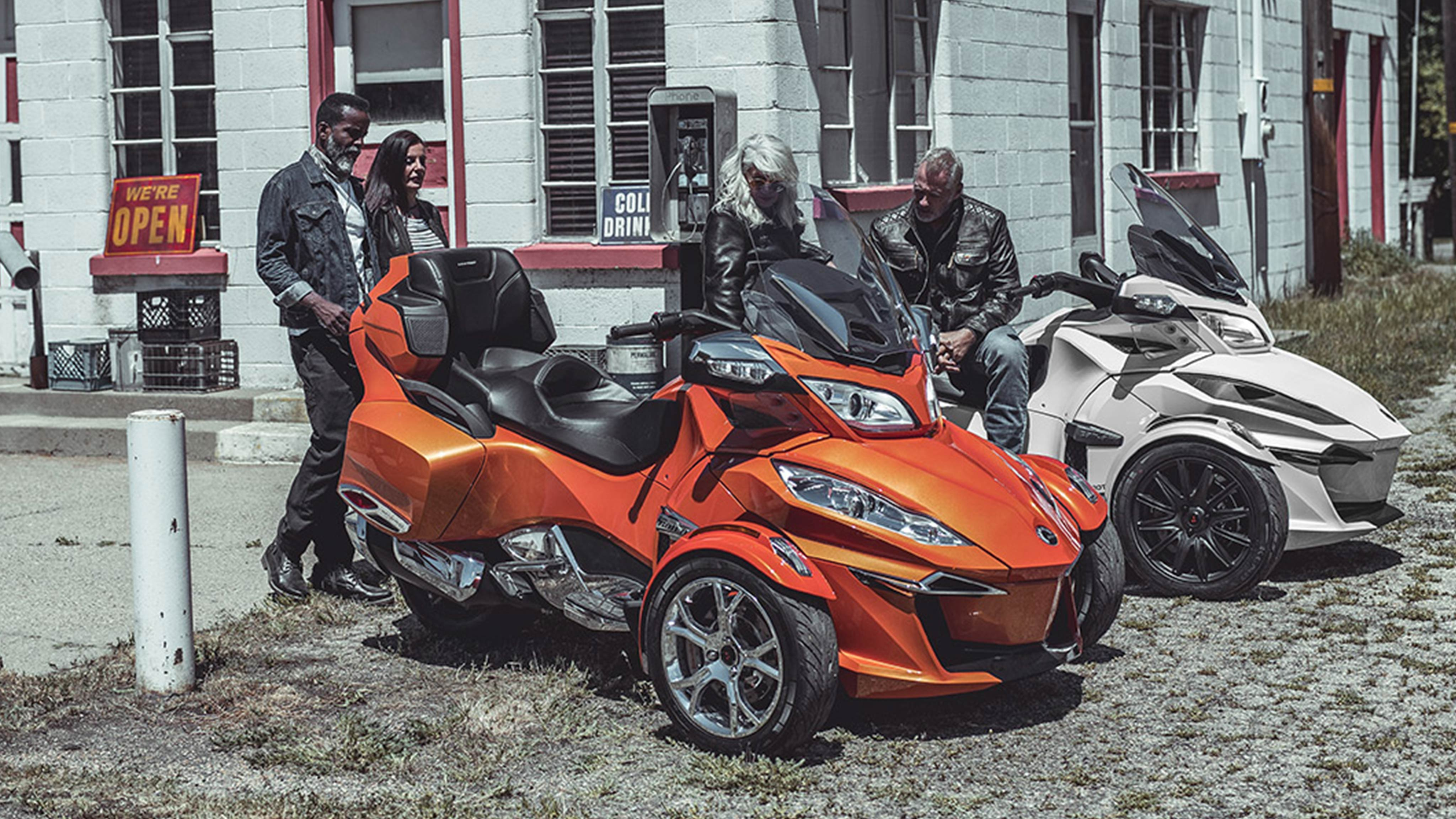 People chatting around 2 2019 Can-Am Spyder RT models, in front of a Gas station