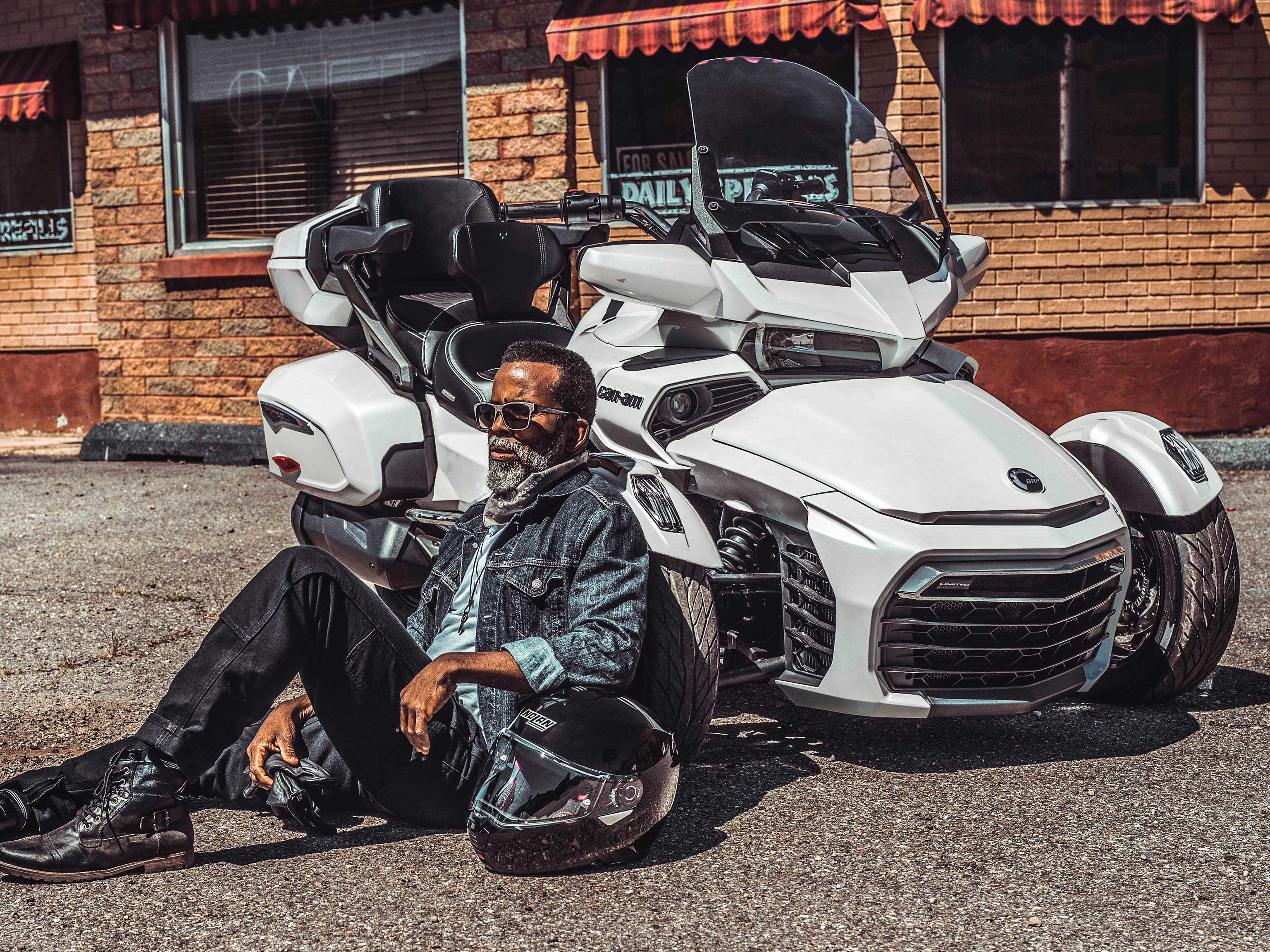 A man on the ground leaning against his parked Can-Am Spyder with an arm resting on his helmet