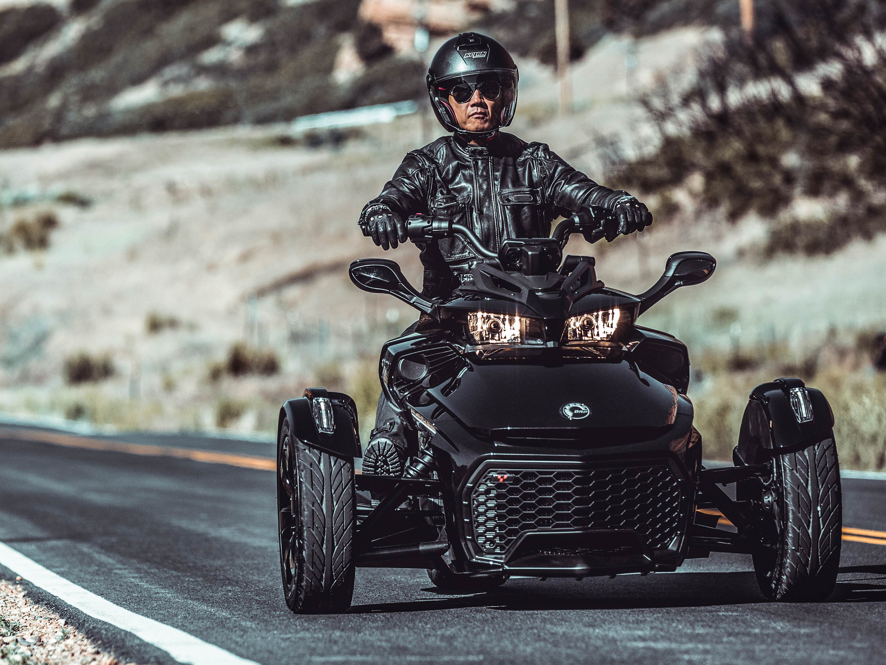 A man riding his Can-Am Spyder along the open desert road