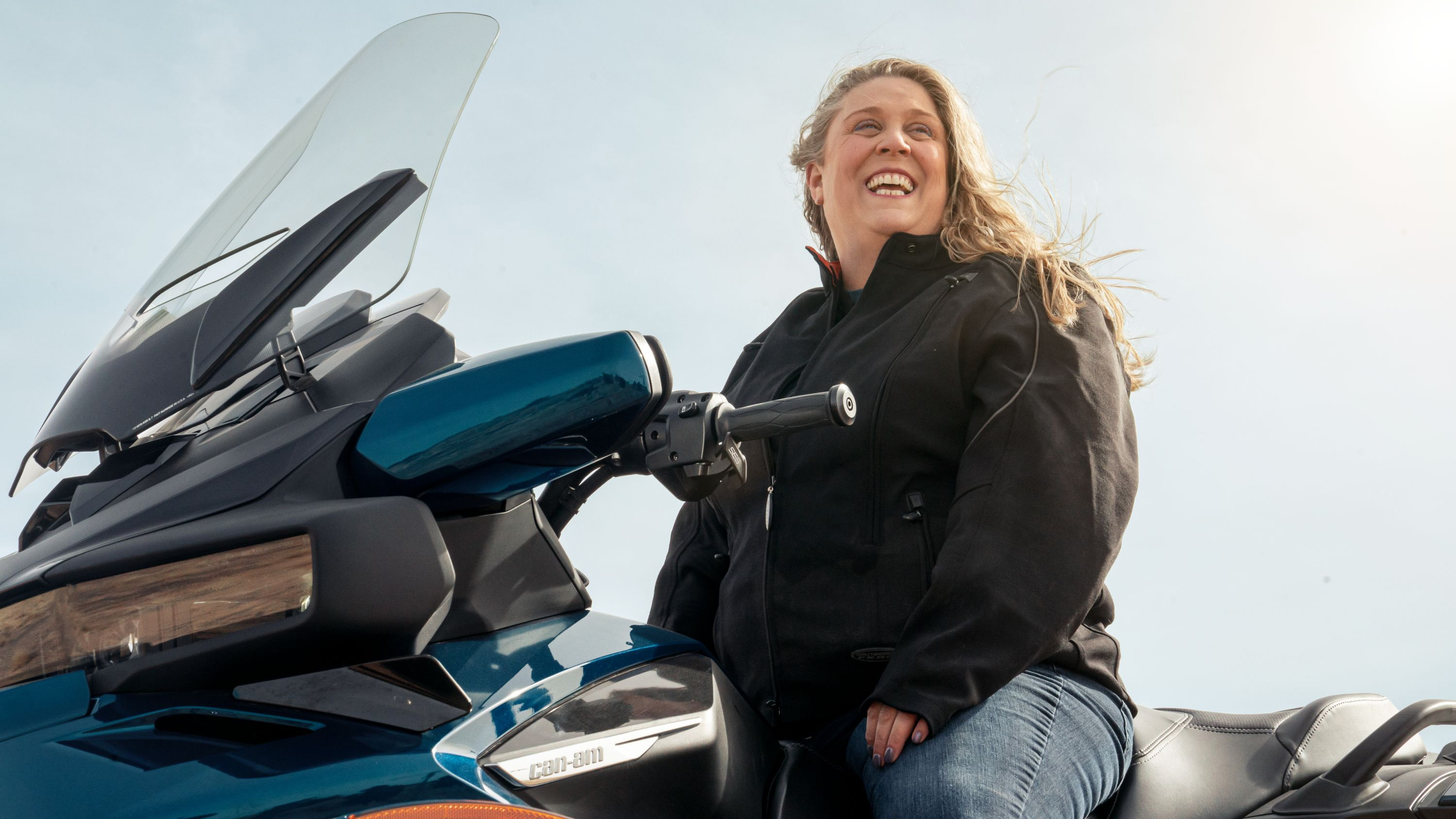 A woman smiling while on her vehicle